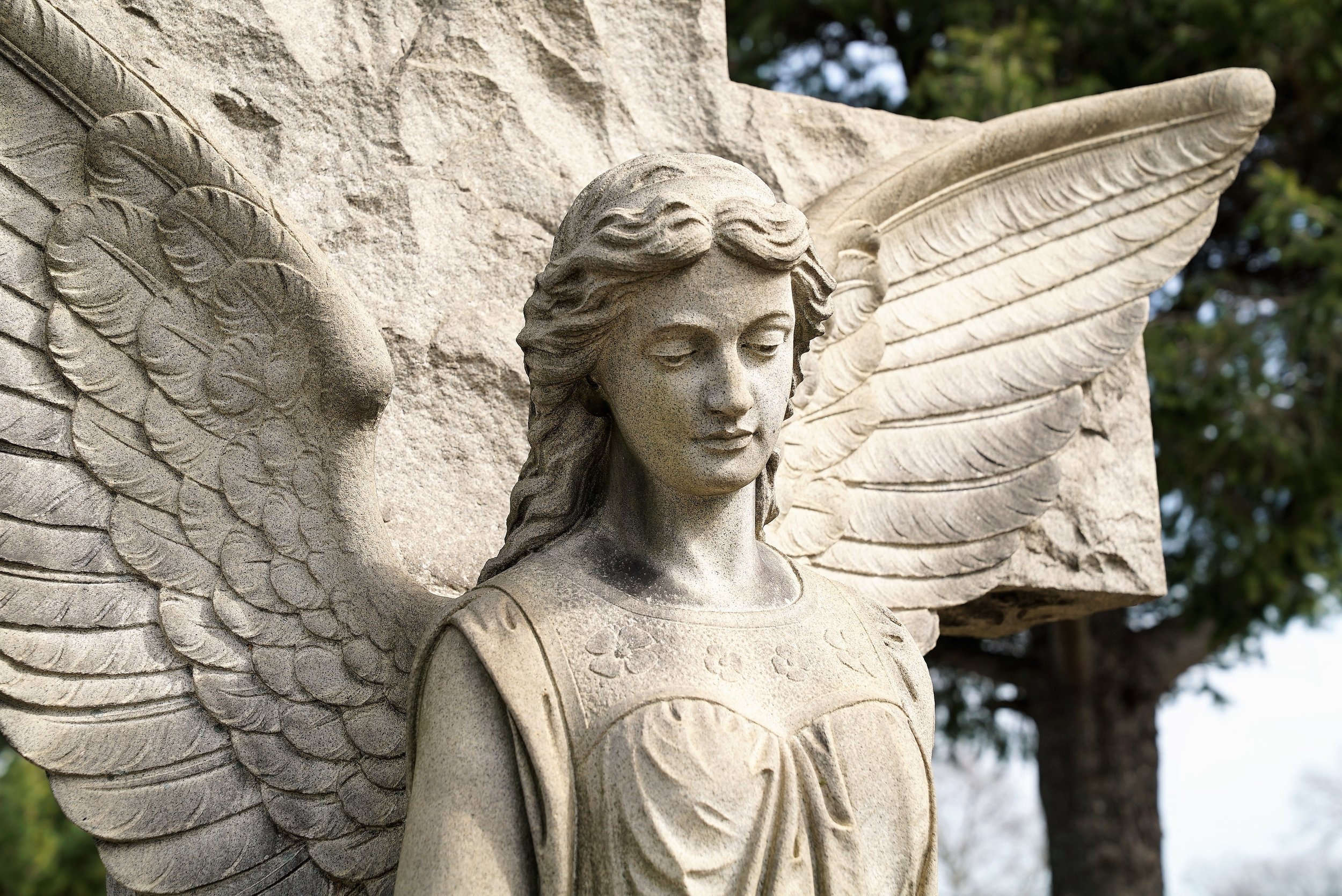 An elaborately carved angel stands over a grave at Holy Cross Cemetery. Yeadon, Pennsylvania.