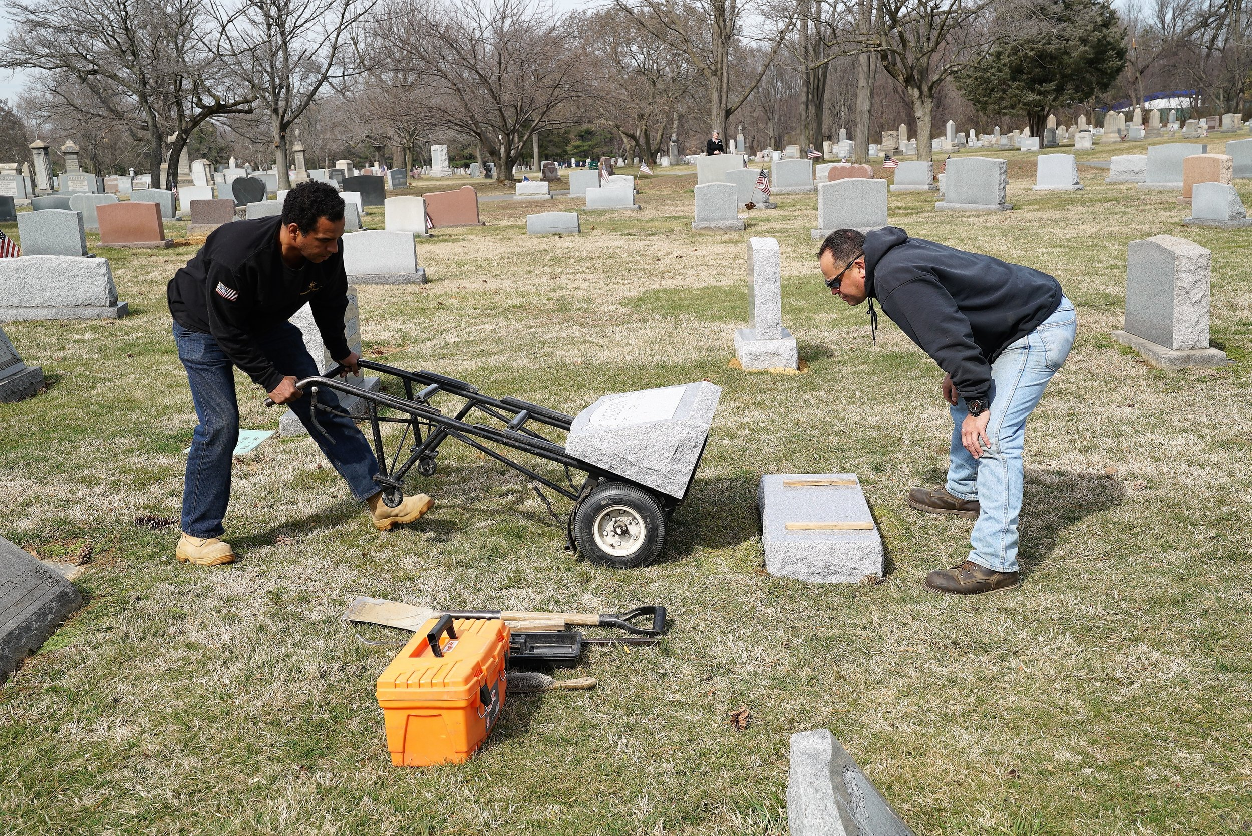 Workers setting a headstone at Lawn Croft Cemetery in Marcus Hook, PA. A cemetery representative exercises attention to detail as she watches from a distance.