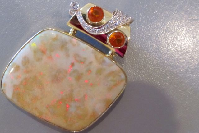 Two-sided pendant. Side A: 18k gold, bezel set Andamooka opal that has been polished front and back. Set with 2 fire opals and 2 diamonds.