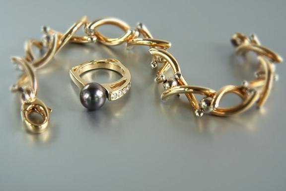18k yellow and white gold tubular twist bracelet and an 18k yellow gold, 10.5mm Tahitian pearl ring with .60 ct. t.w. full cut diamonds (VS1, G)