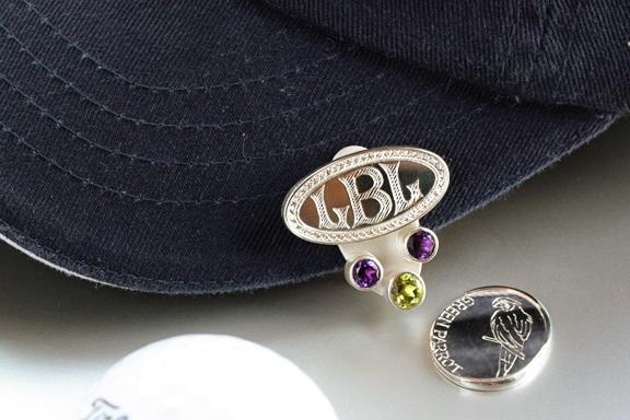 Hand engraved, magnetic sterling silver golf ball marker with amethyst and peridot. Clip it to your hat visor and detach the ball marker as you need it. Can be customized and created for men or women.