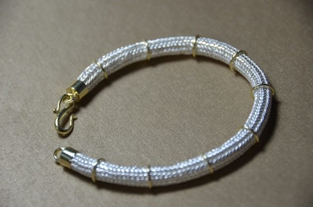 Handmade in America sterling silver and 22kt yellow gold bracelet includes 6 strands of silver and 22kt yellow gold rings evenly spaced throughout. Clasps are also hand made. 
