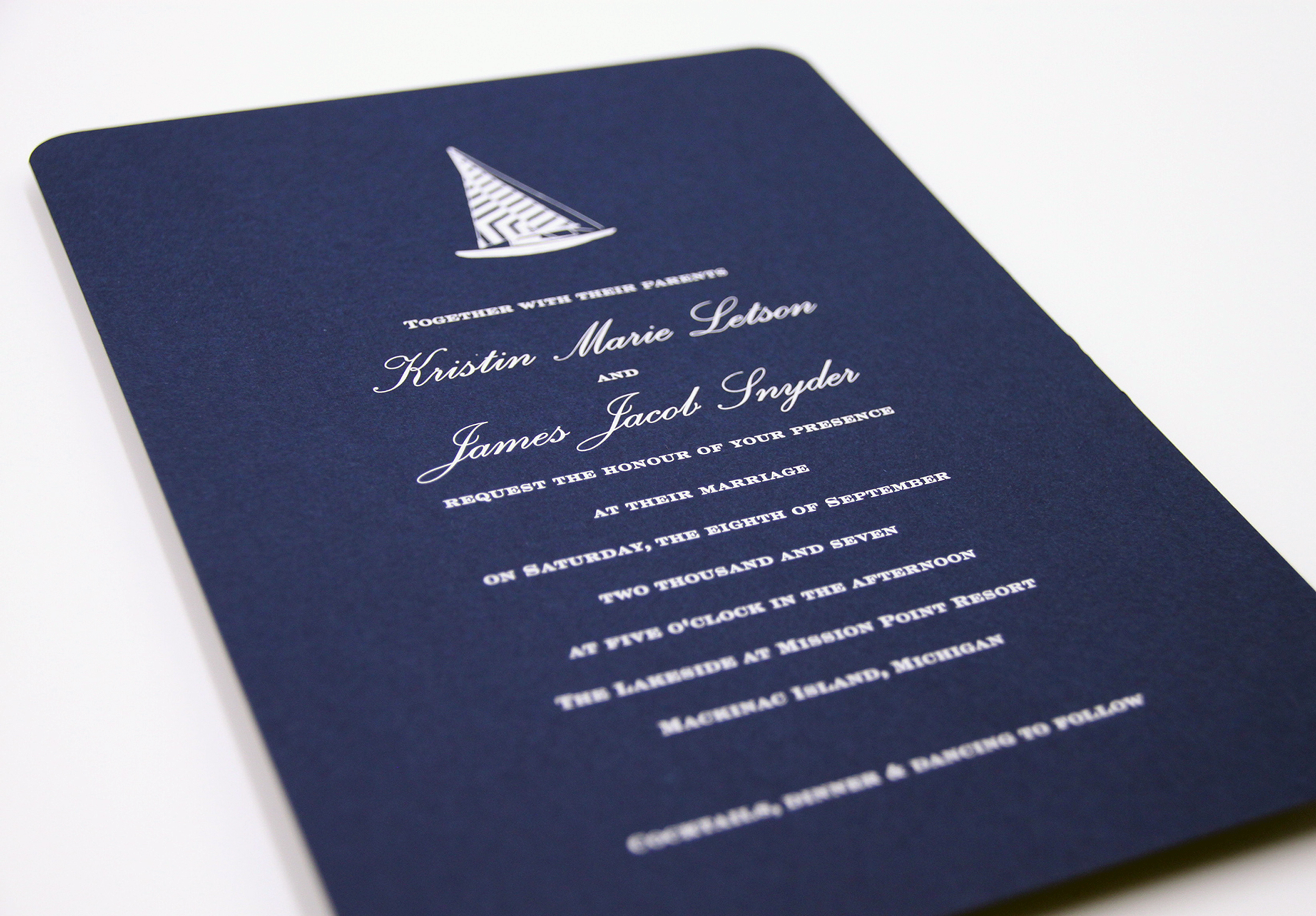 Nautical inspired wedding invitation with custom sailboat motif. Engraved in white ink on navy linen paper.