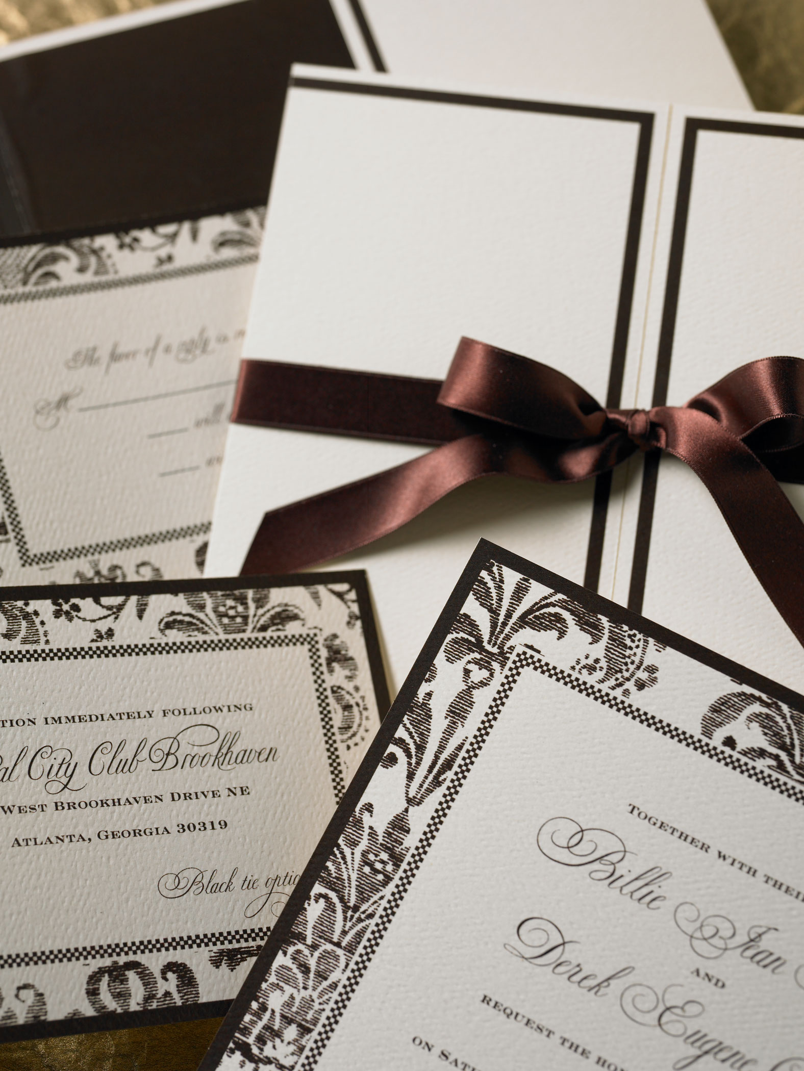 Layered vintage damask wedding invitation, reception card and response card flat printed in chocolate brown ink on soft white felt weave paper. Pearlized invitation jacket with satin ribbon. Chocolate brown envelopes.