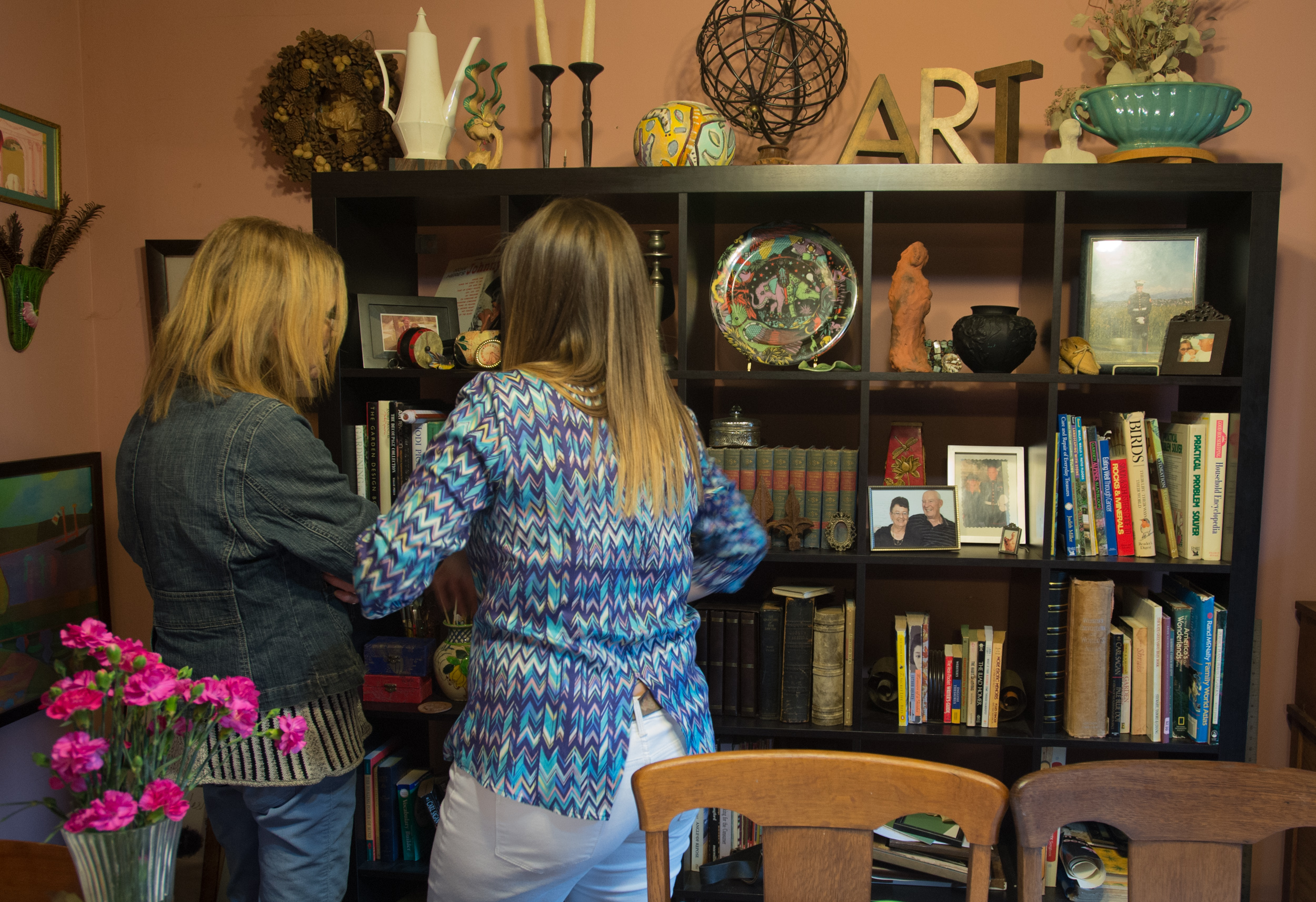 Carol shows a relative her collection of trinkets and artwork on a bookcase in her house on Easter Sunday, Apr. 5, 2015.
