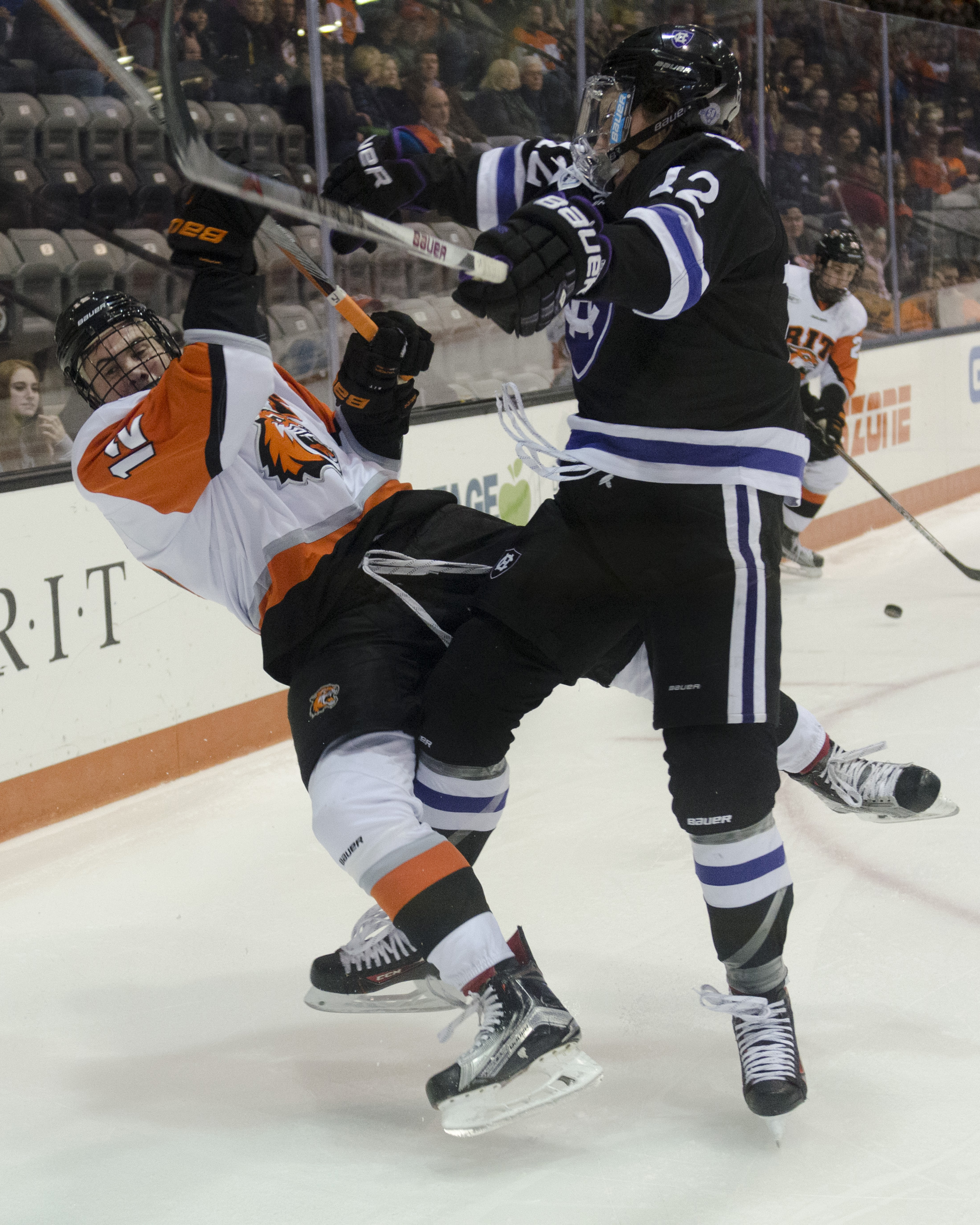Holy Cross forward Scott Pooley delivers a body check to Rochester Institute of Technology defenseman Greg Amlong during a regular season game in Rochester, N.Y. on Saturday, Jan. 30, 2016. The two teams tied 3-3, following a previous tie of 2-2 the night before.