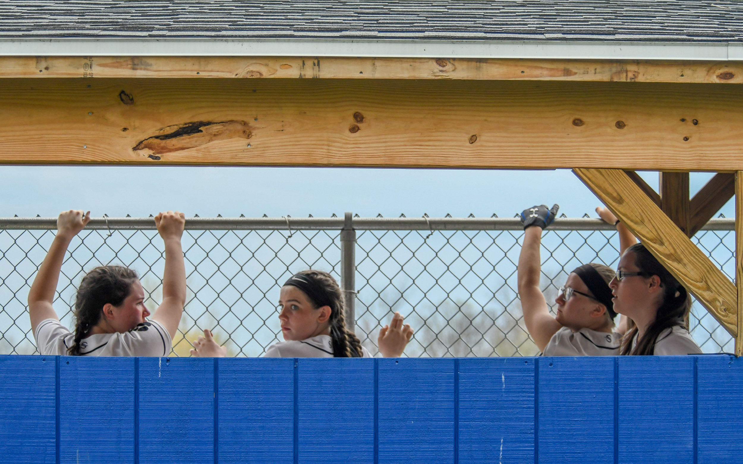 Cohoes varsity softball players grasp the outer fencing of the dugout during a game against Greenfield at Cohoes High School in Cohoes, N.Y., on Thursday, May 3, 2018.