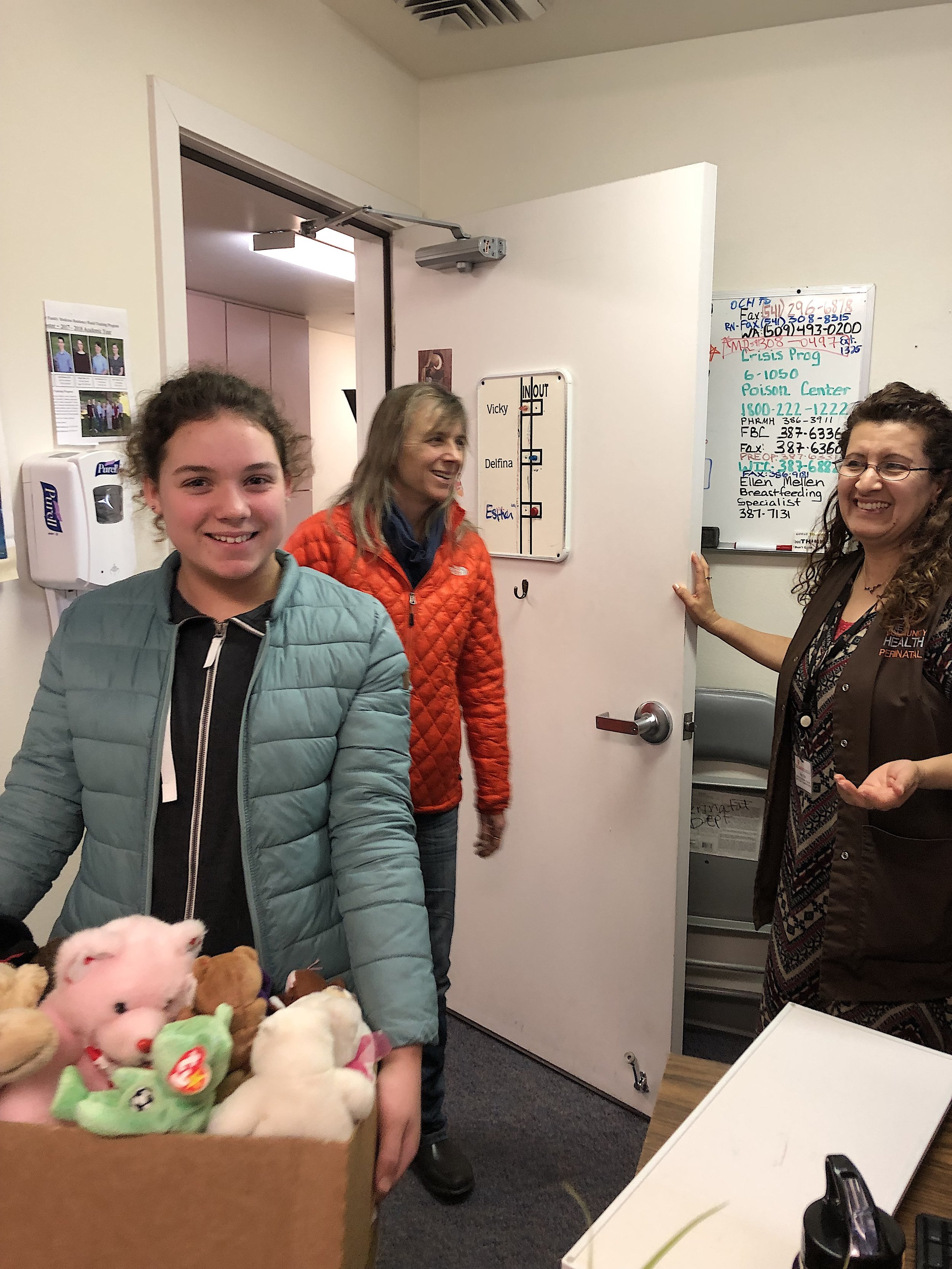 Amy Elliott of White Salmon, Wash., (left), along with her mom, Caroline Elliott (center), drop off a box of stuffed animals to Vicky Valle (right), certified community health worker at One Community Health.