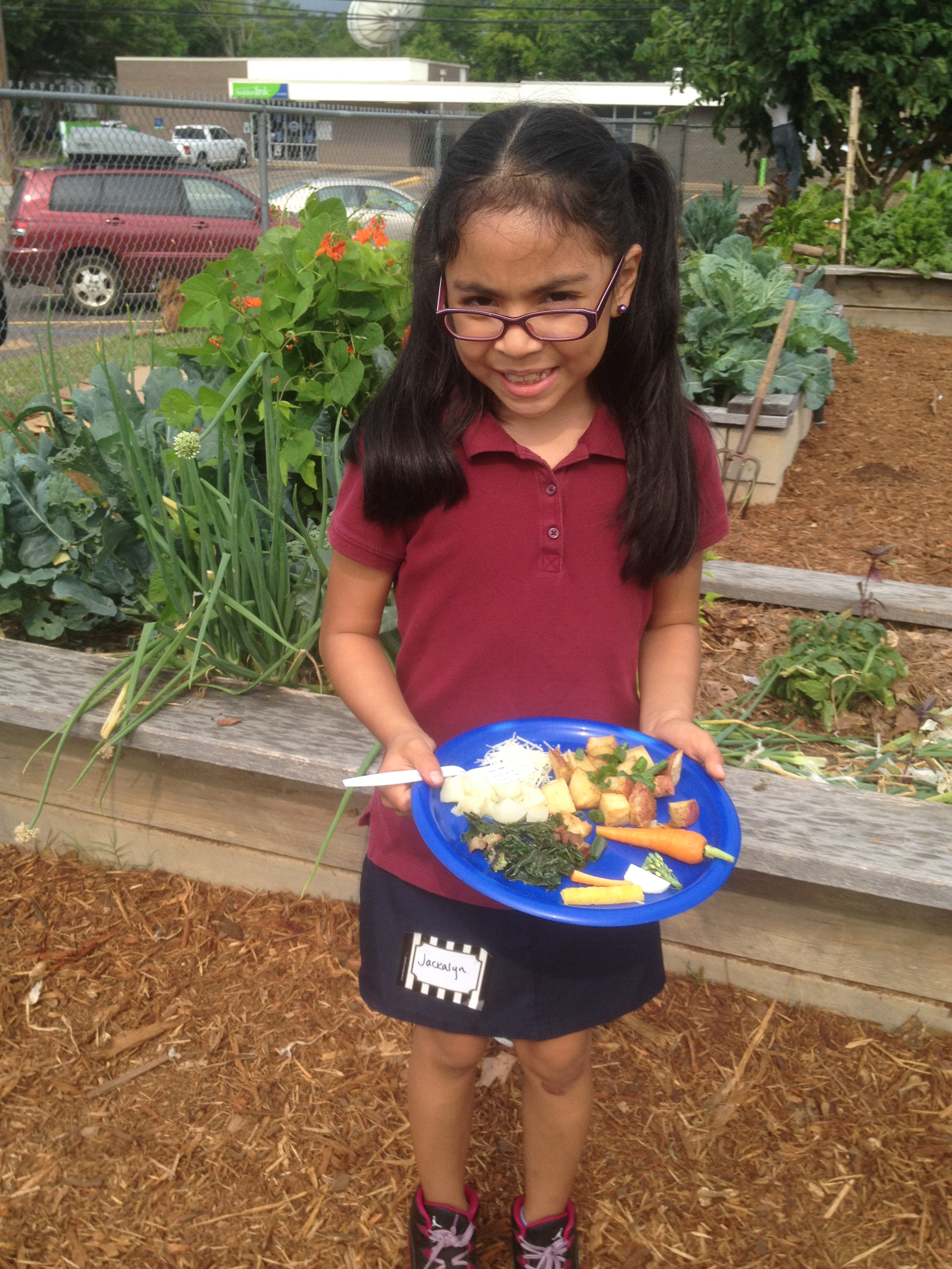 2nd Grader at TJR is excited to try new vegetables at the end of the season Harvest Feast.