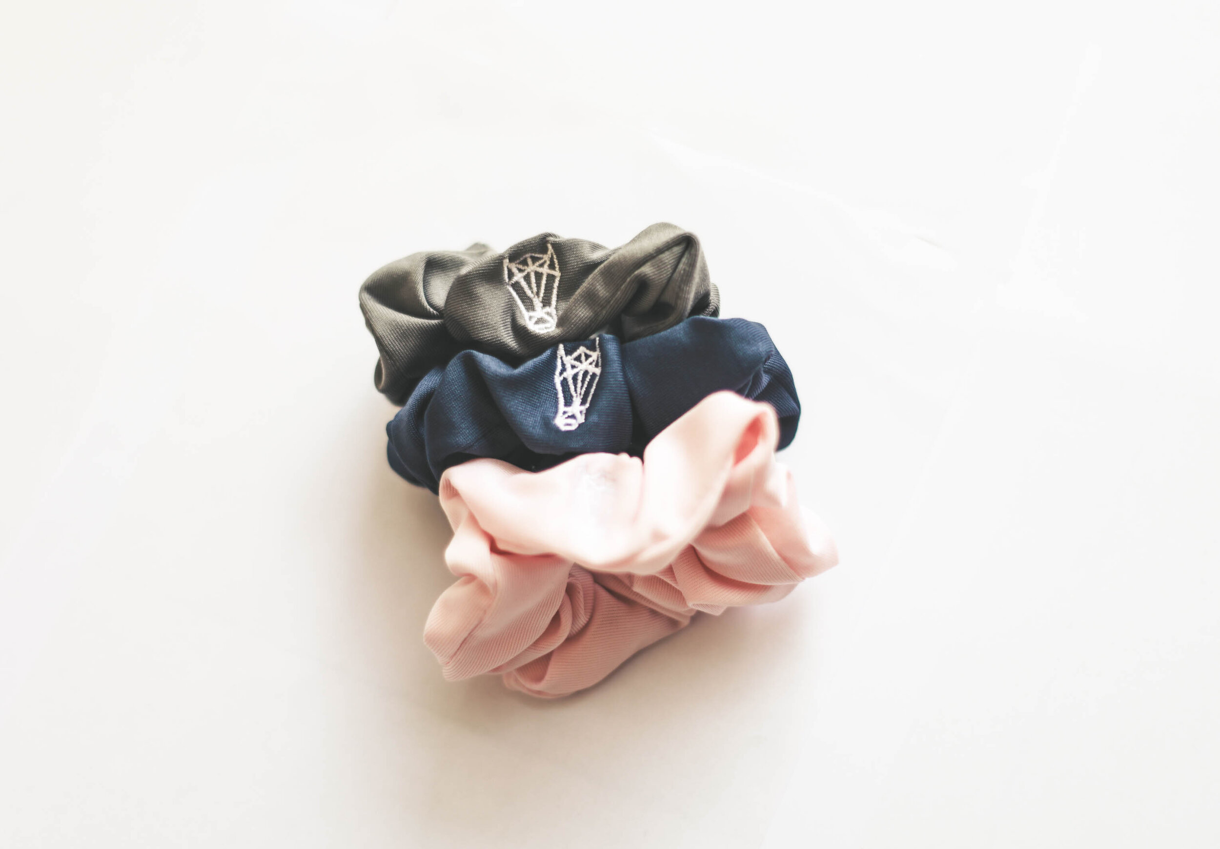 Set of Three scrunchies in Vancouver Grey, Aegean Blue, and Champagne Pink.