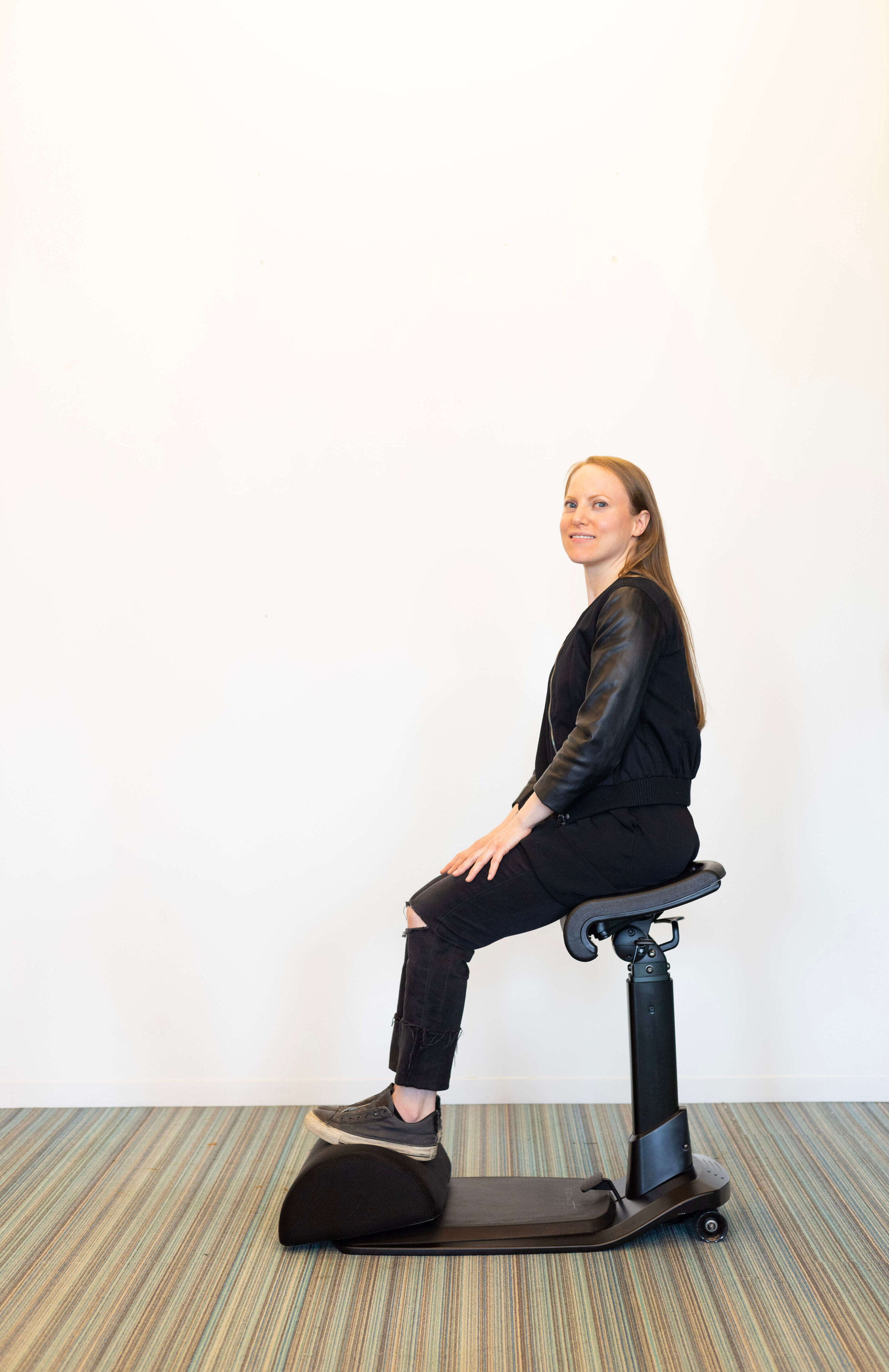A cushion footrest + adjustable-height chair in sitting position: The ErgoFoam Ergonomic Under Desk Foot Rest complements our LeanRite™ Elite standing desk chair perfectly