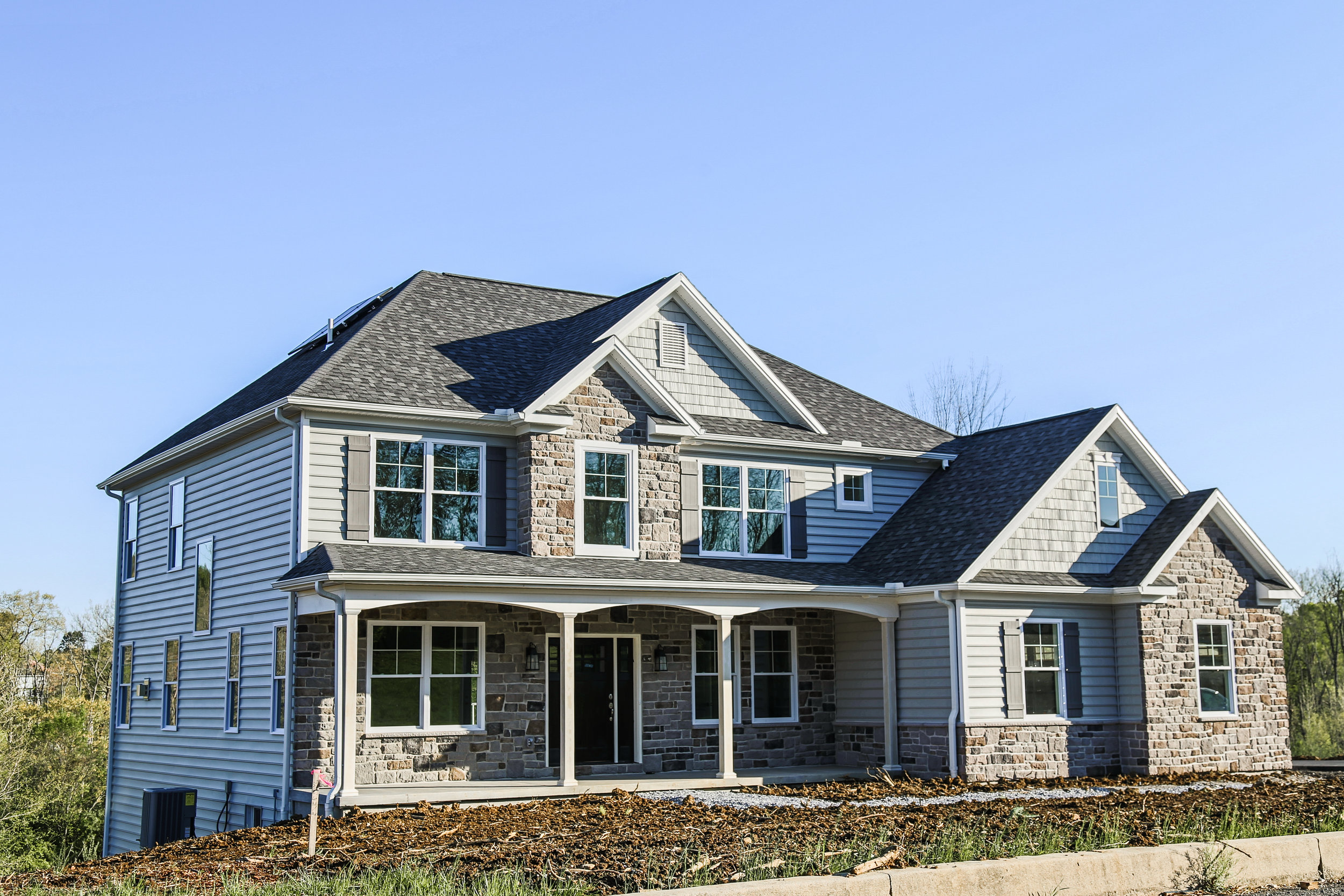Beautiful stone work and hip roof design, full front porch and solar package featured