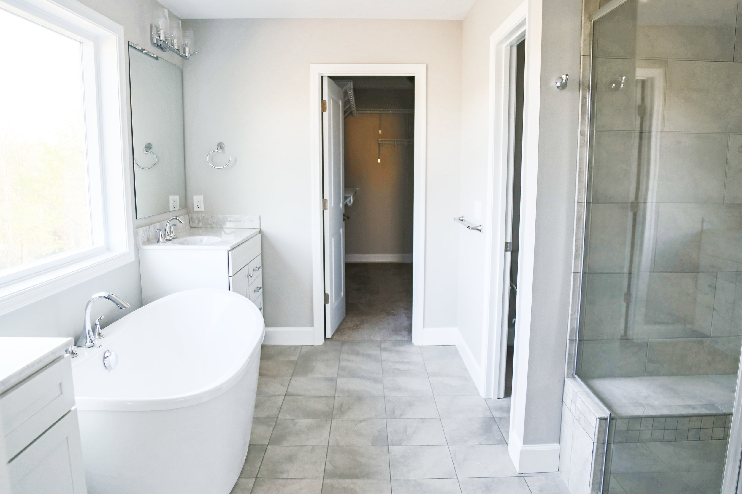 Luxurious Bathroom Design with a slipper tub, split vanity and tile walk-in shower