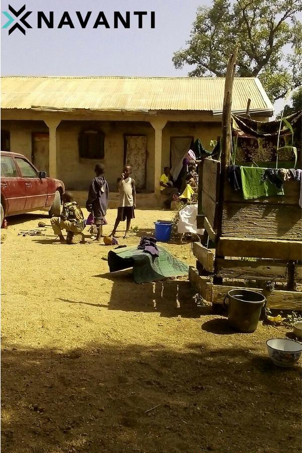 Youth in front of household in Vi Village, Michika LGA