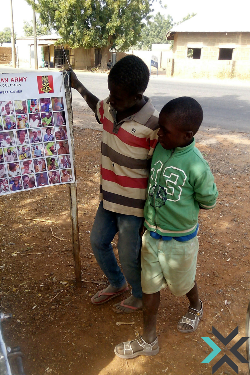 Children looking at the poster of most wanted Boko Haram members posted in Kofar Jauro