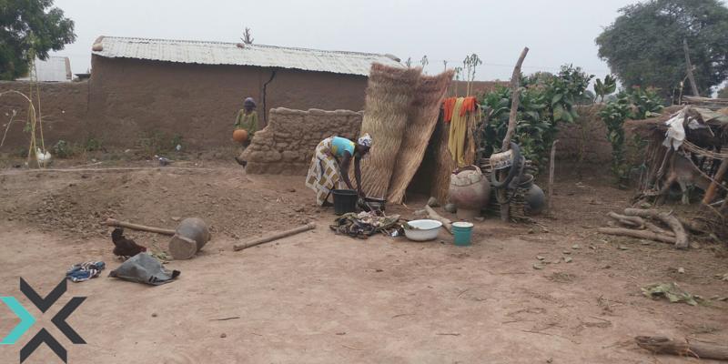 A woman washing clothes outside of her home in Kofar Yanga ii