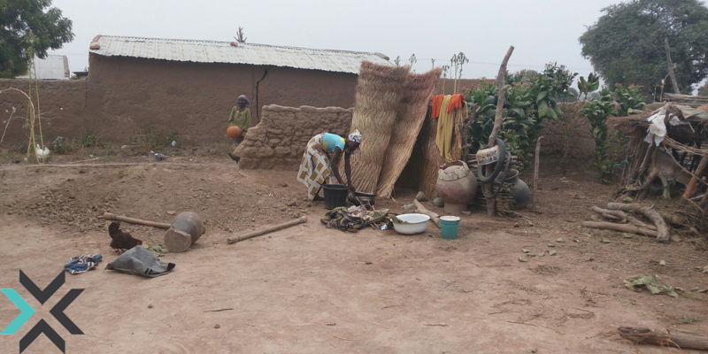 A woman washing clothes outside of her home in Kofar Yanga ii