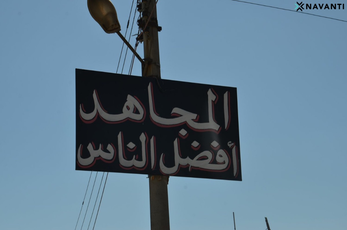 """A sign in Idlib reads, """"The Holy Warrior is the Best Sort of Person."""" Source: Navanti"""