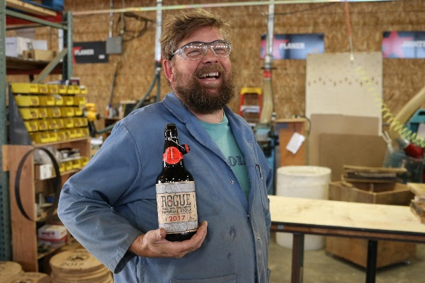 Rogue's Rolling Thunder Barrel Works Master Cooper, Nate Lindquist, poses with Rolling Thunder Imperial Stout