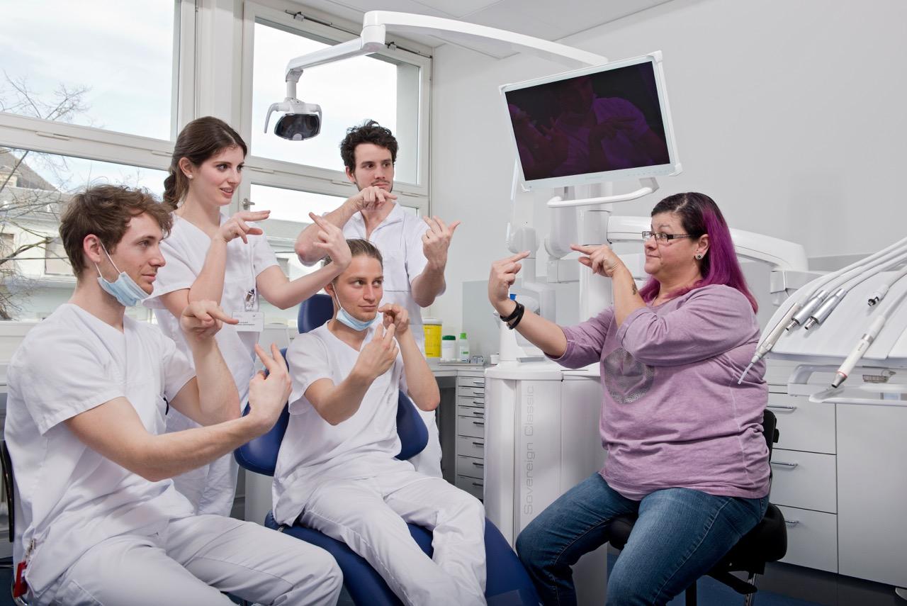 Eine gehörlose Frau sitzt im Behandlungszimmer vier Studierenden gegenüber, welche eine Gebärde einüben, die ihnen gezeigt wird.