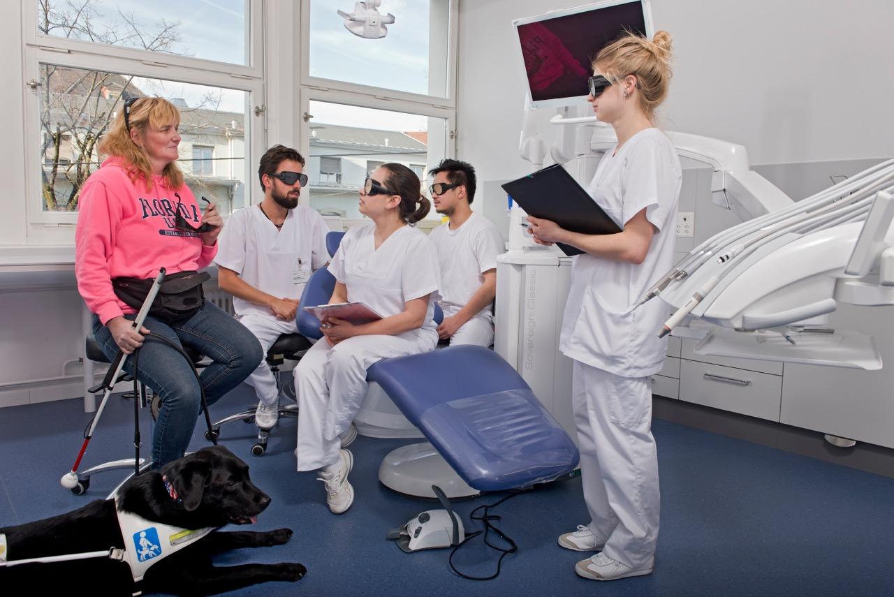 Eine Frau mit Sehbehinderung erklärt Studierenden, worauf bei der Kommunikation zu achten ist, wenn die Sehfähigkeit eingeschränkt ist.