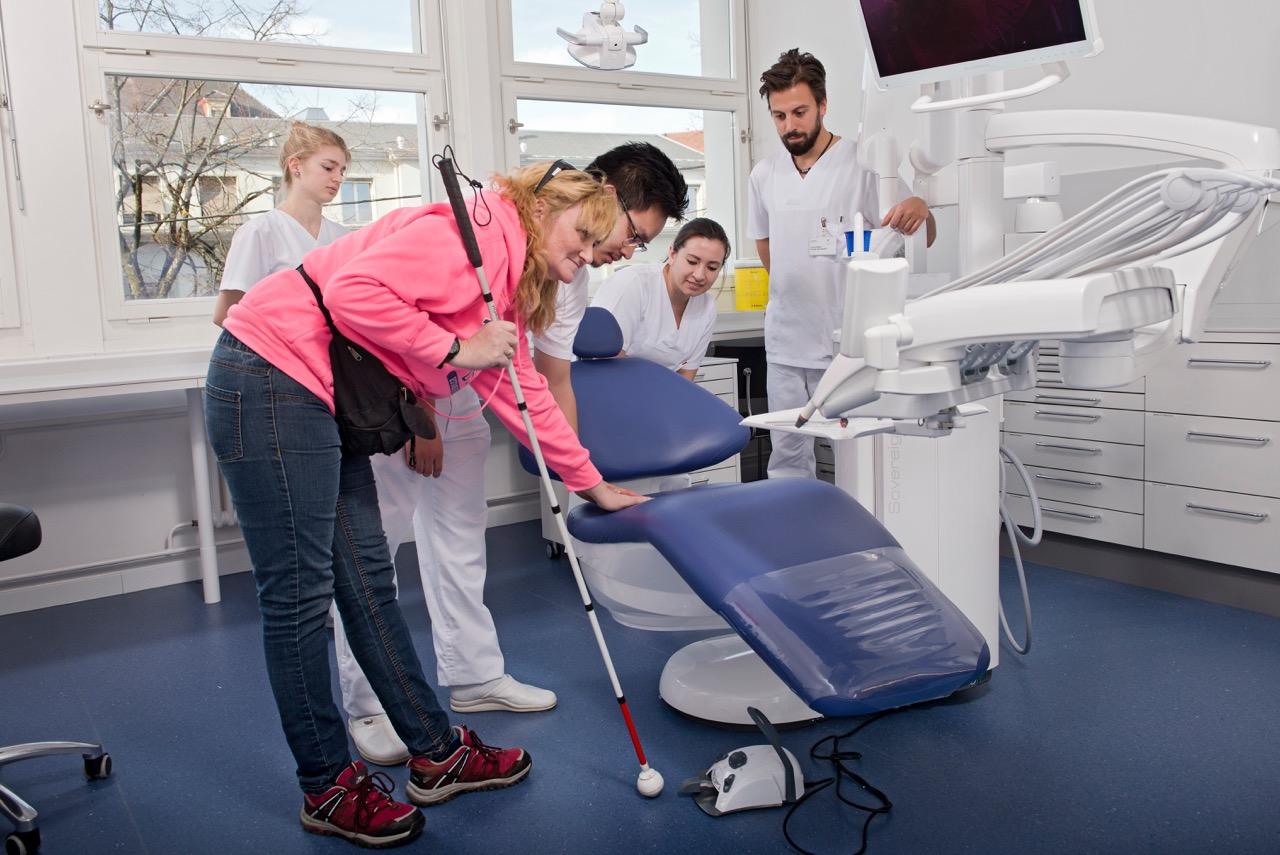 Eine Frau mit Sehbehinderung, mit Langstock, ertastet einen Behandlungsstuhl mit Unterstützung eines Studierenden.
