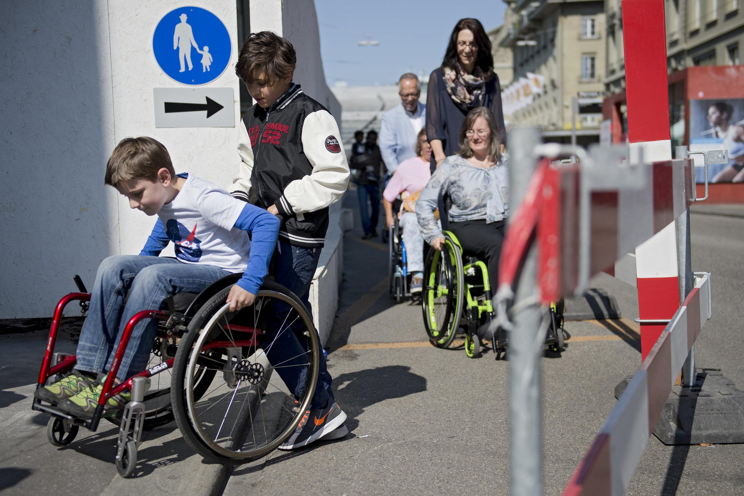Auf einer Baustellen versucht ein Kind im Rollstuhl mühevoll den Absatz aufs Trottoir zu überwinden