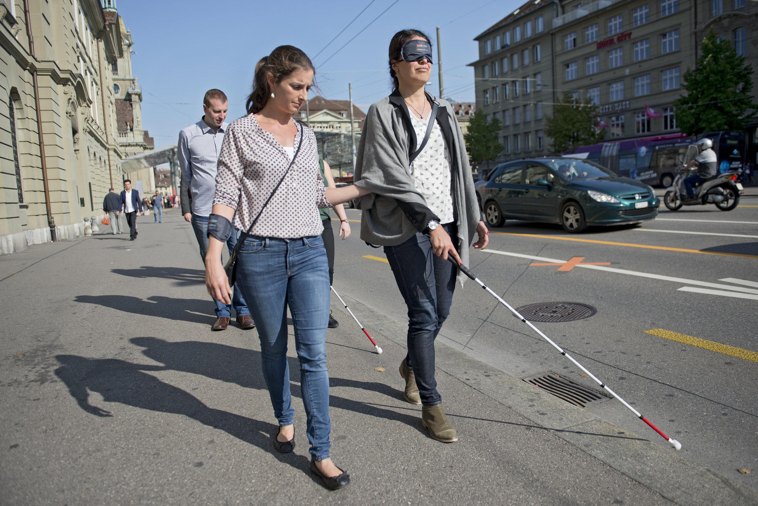Eine Frau mit Dunkelbrille wird von einer anderen Kursteilnehmerin am Arm geführt und ertastet mit dem Langstock den Trottoirrand