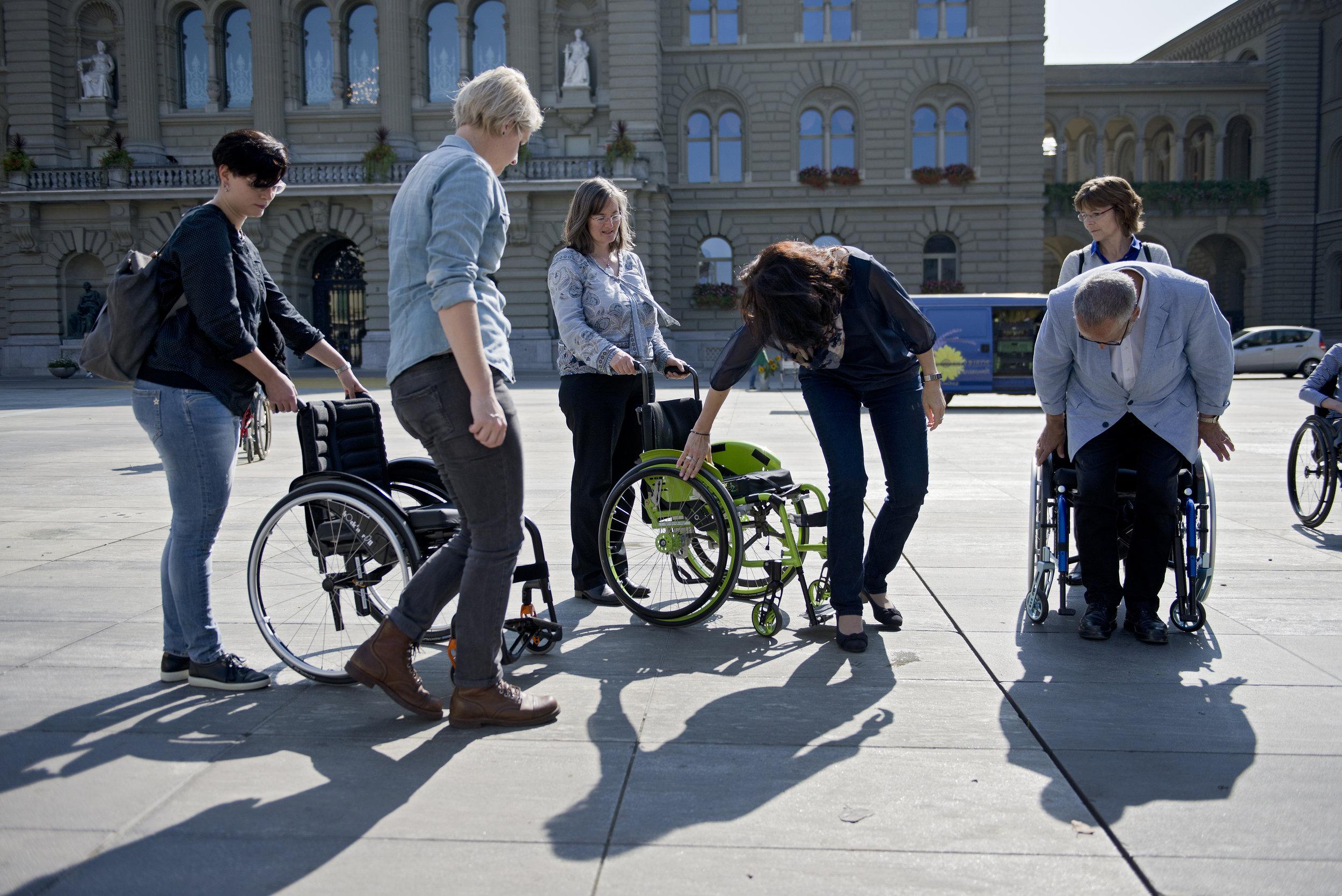 Eine Gruppe von Kursteilnehmenden übt das Ein- und Aussteigen aus dem Rollstuhl