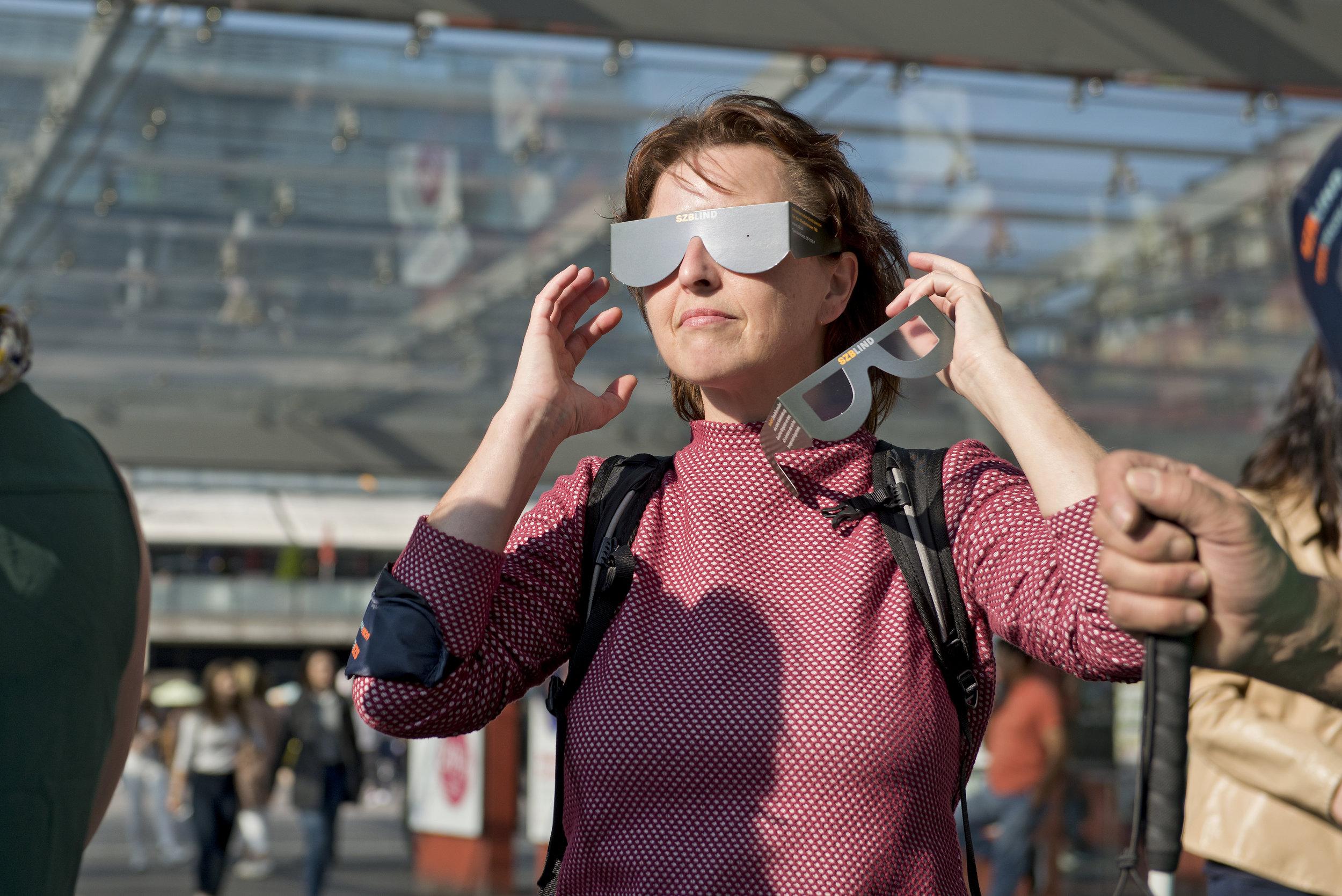 Eine Frau mit Simulationsbrille versucht, in der Ferne etwas zu erkennen.