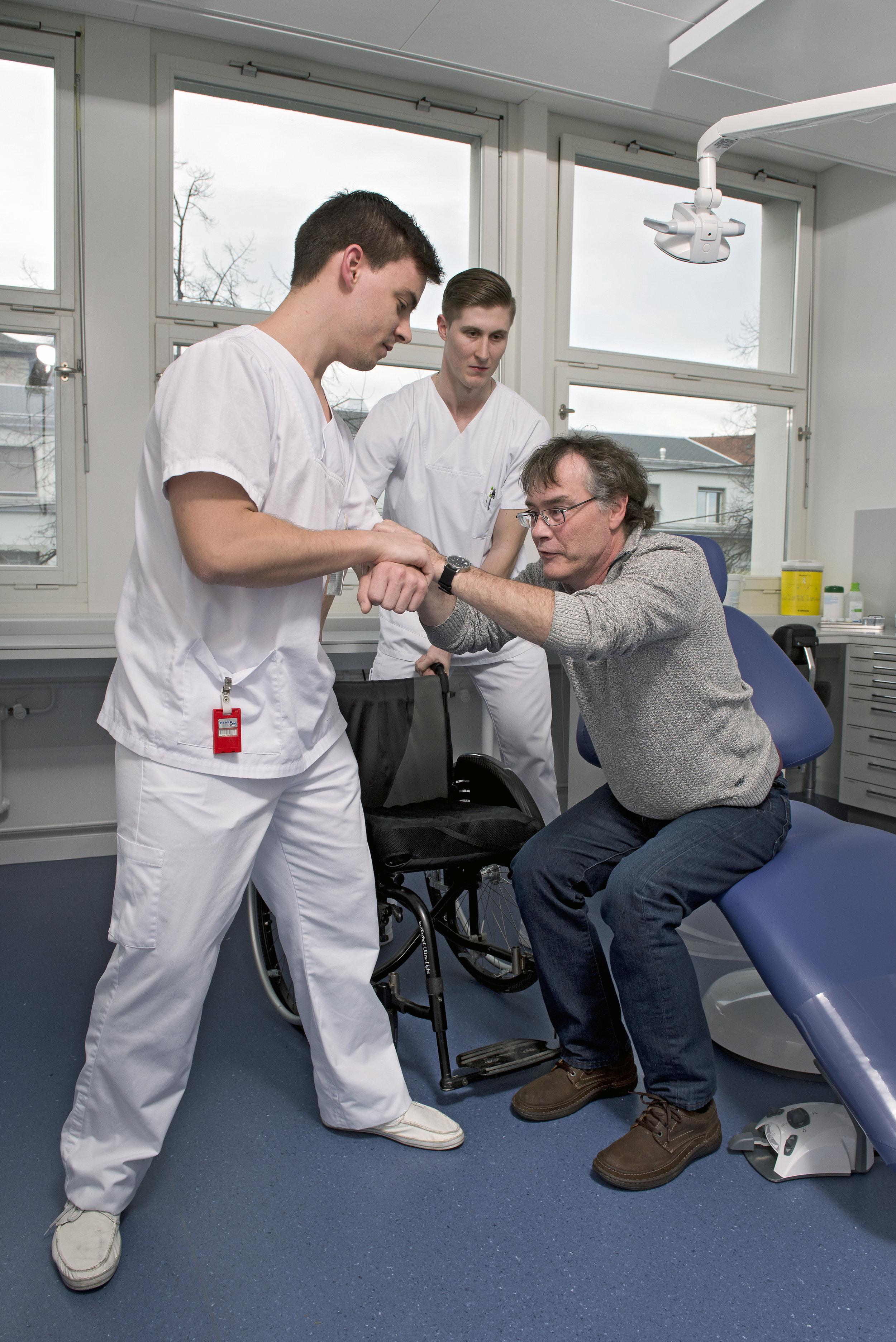 Ein Student hilft einem Mann mit Gehbehinderung beim Umsitzen vom Behandlungs- auf den Rollstuhl.