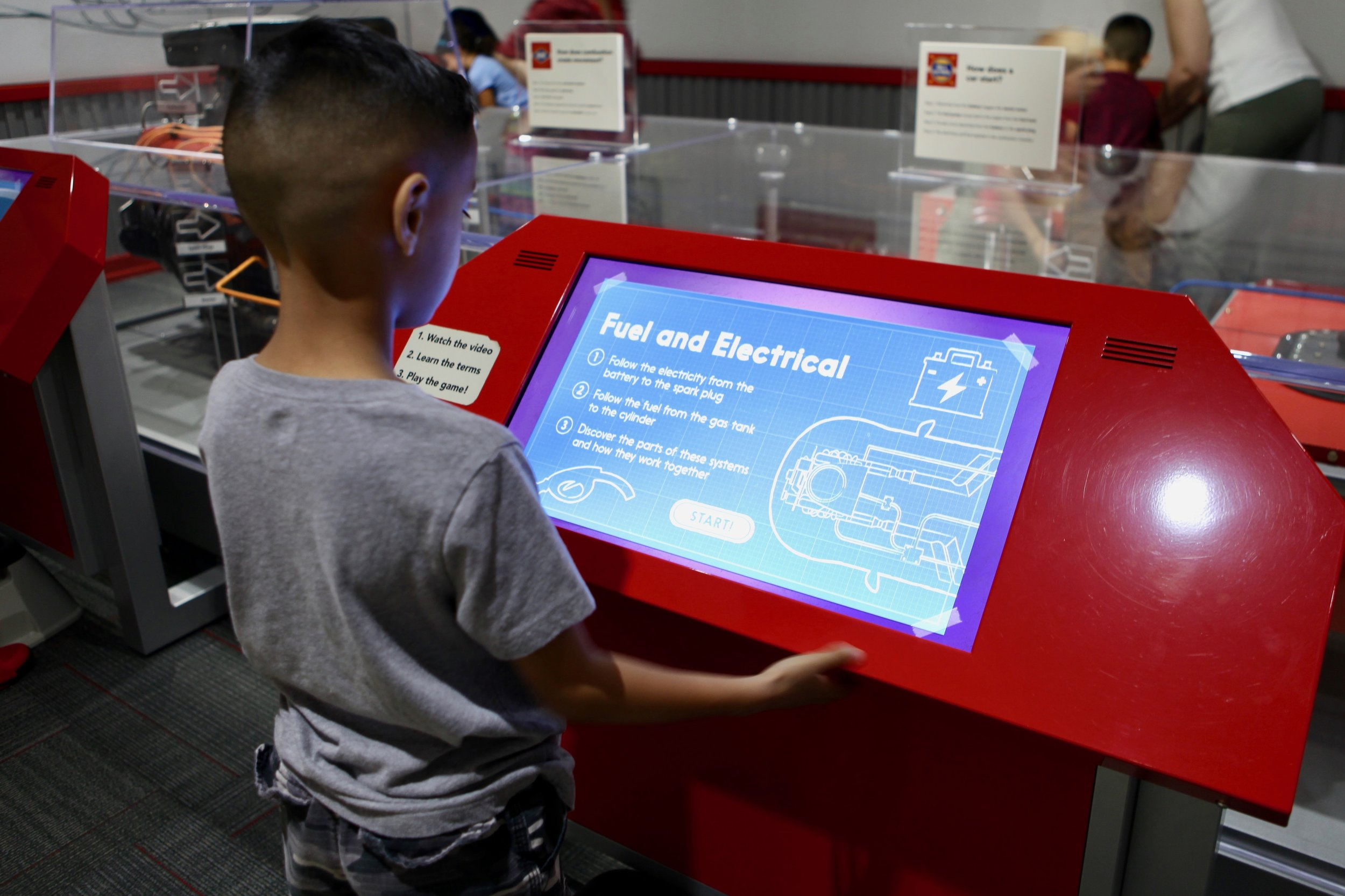 A child learning about the fuel and electrical workings of a car inside the Petersen Automotive Museum Discovery Canter.