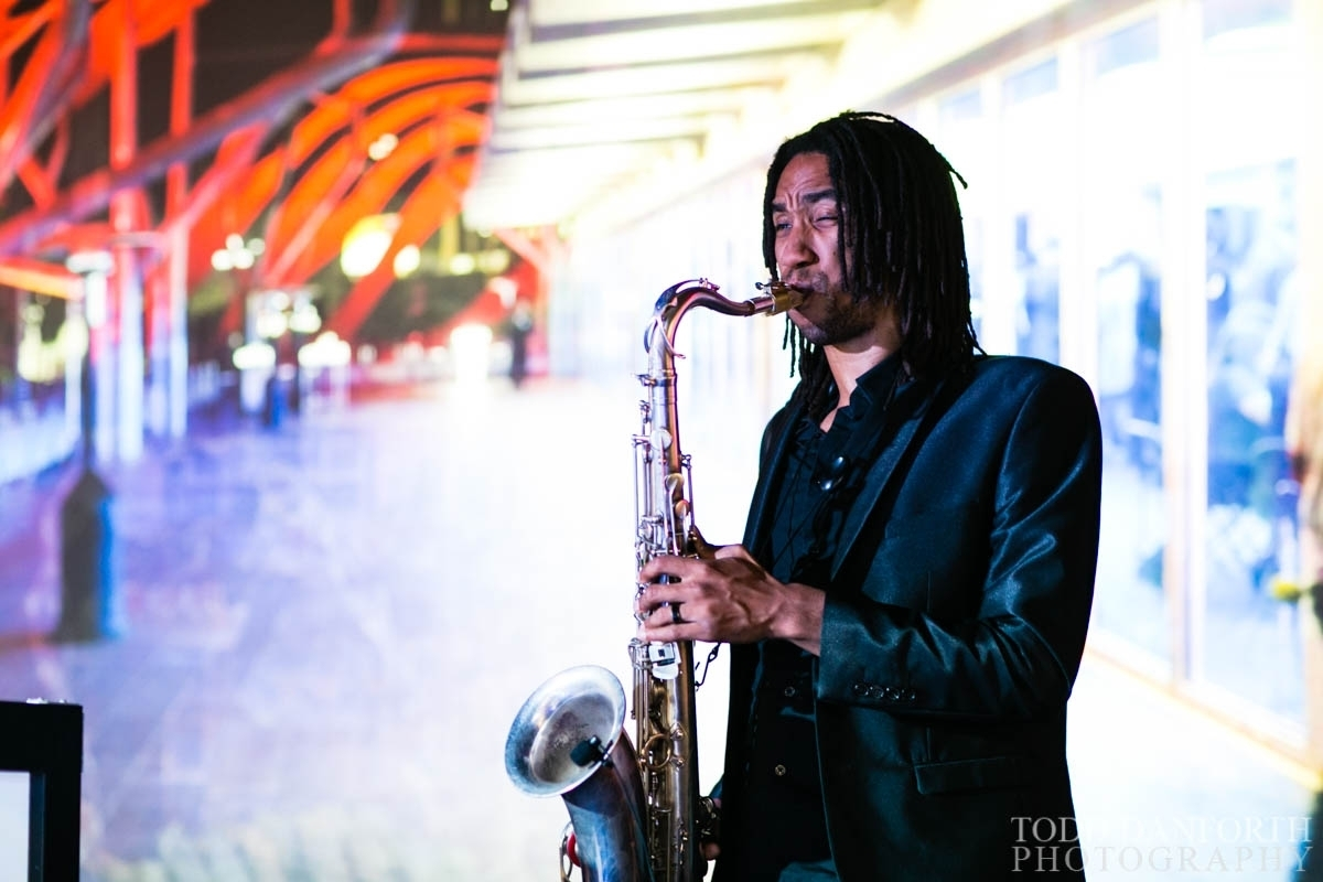 A musician playing the saxophone at an event at the Petersen Automotive Museum.