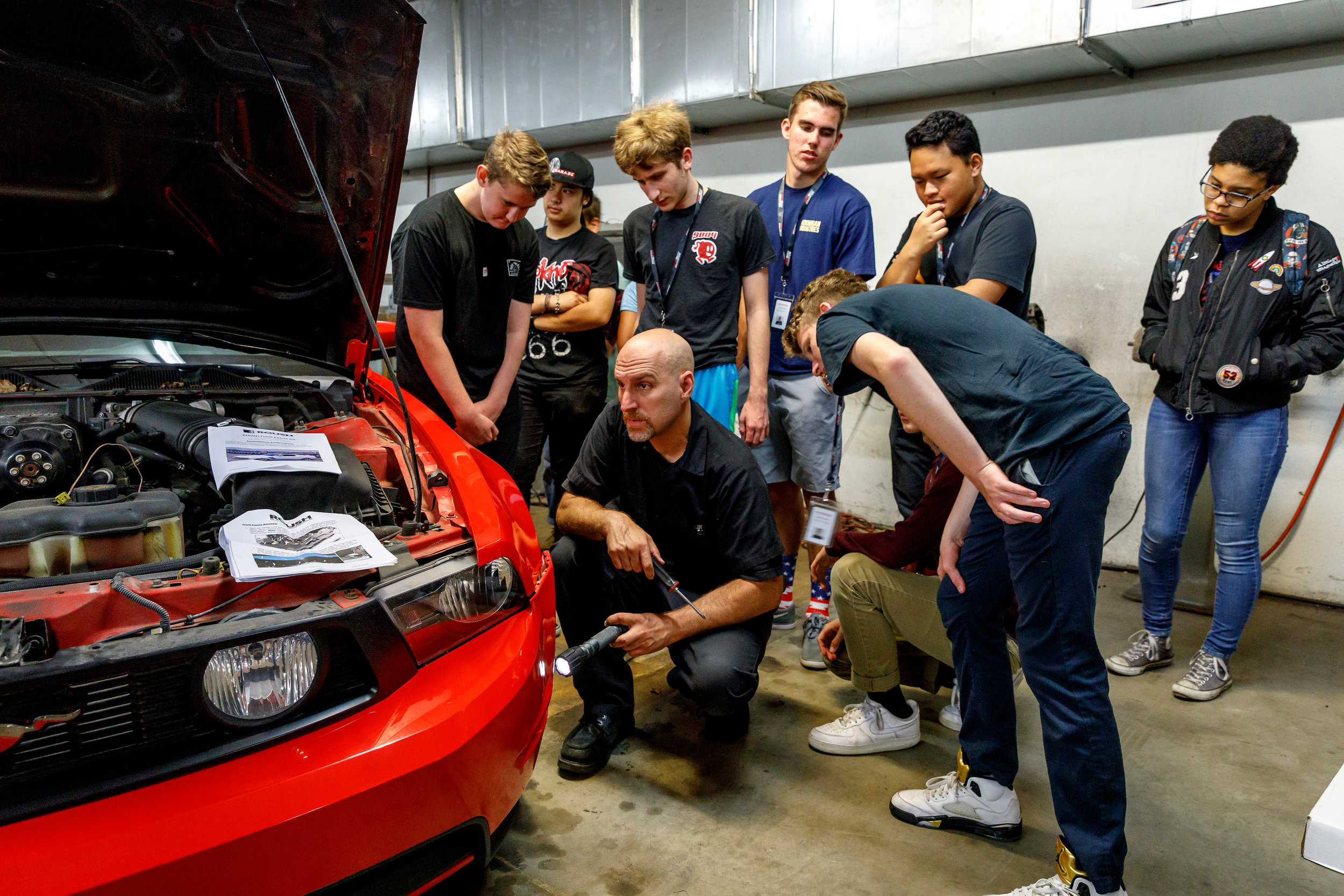 Teens examining the engine of a car with a Petersen Automotive Museum mechanic during the Teen Auto Workshop.