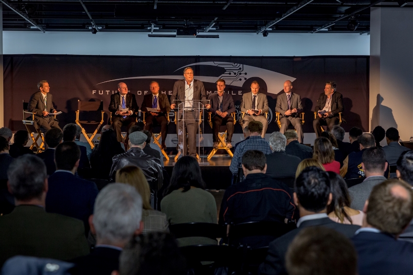 A panel speaking to a crowd during the Future of the Automobile Conference.