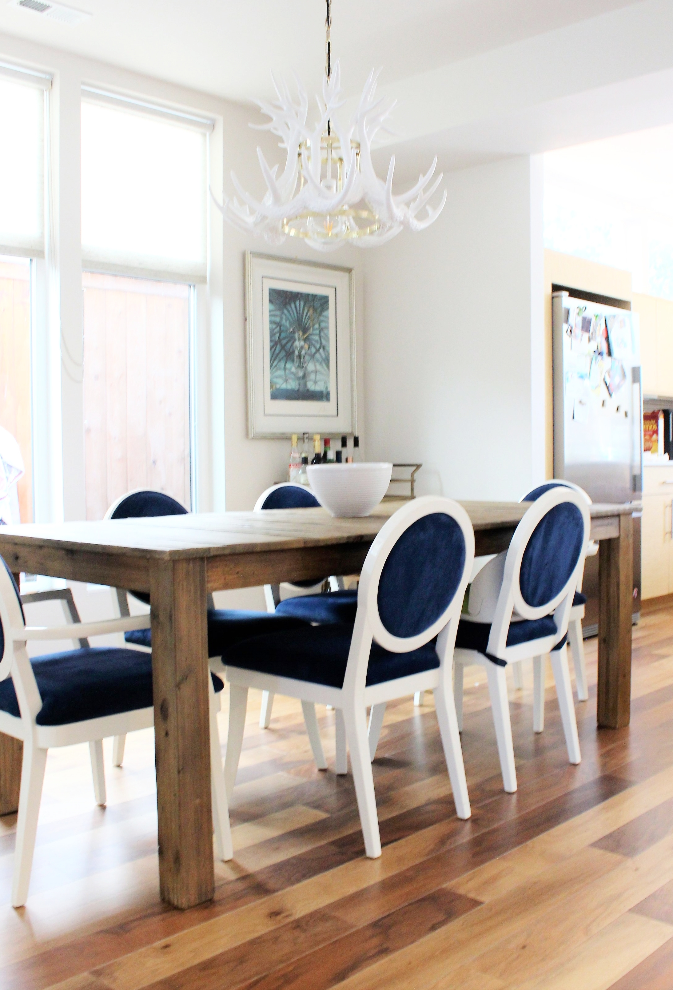 The contrast of this rustic wood dining table and the crisp white and cobalt velvet seating gives this dining room an eclectic, yet sophisticated look. Notice the booster seat added to one of the chairs so their toddler can join them at the table.