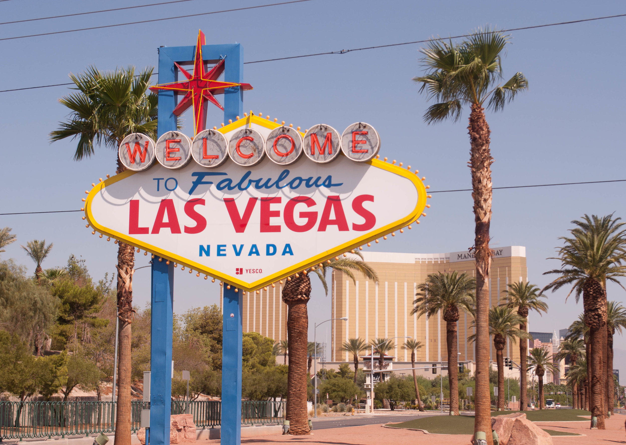 The Las Vegas Sign with palm trees and the Mandalay Bay hotel in the background