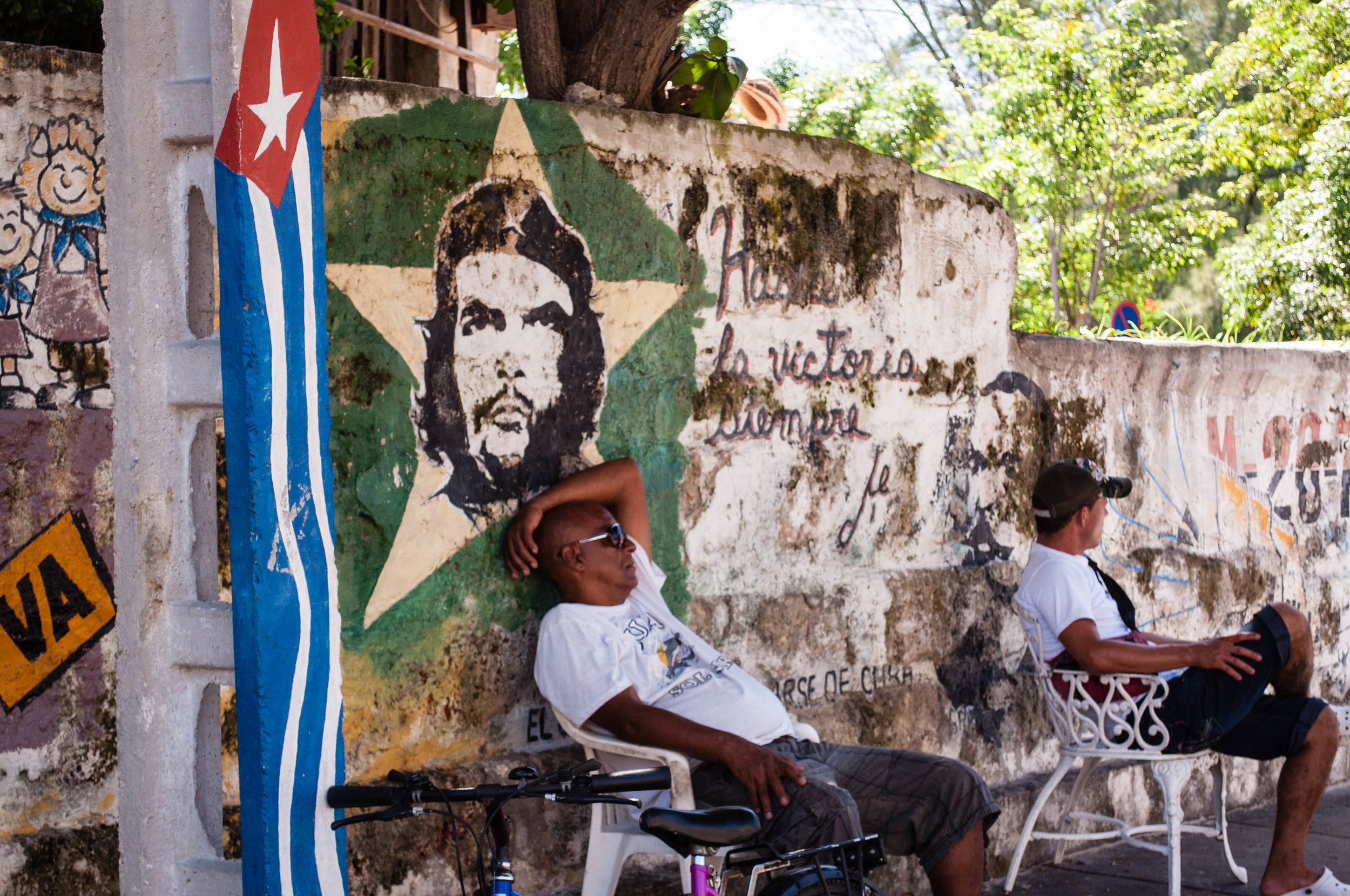 Decaying mural with a Cuban flag and the portrait of the Che with a star in the background on a wall with two men sitting in front. Scene seeing during our day trip to La Havana