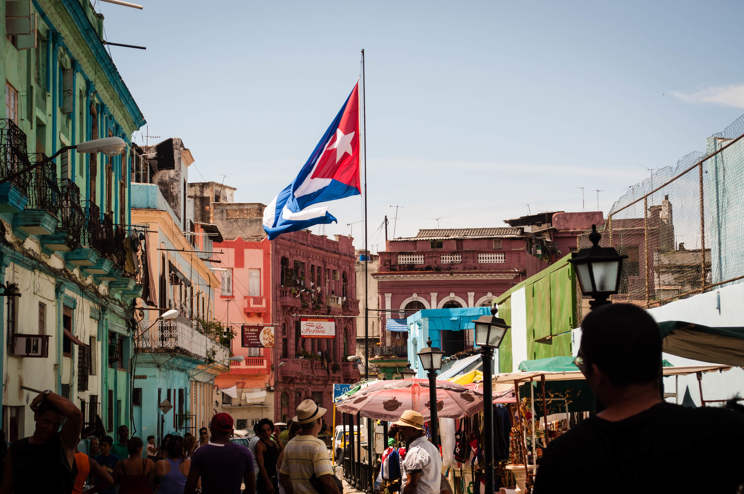 Giant Cuban flag in a large busy avenue with tourist surrounded by colourful buildings. This scene was seen during our day trip to La Havana
