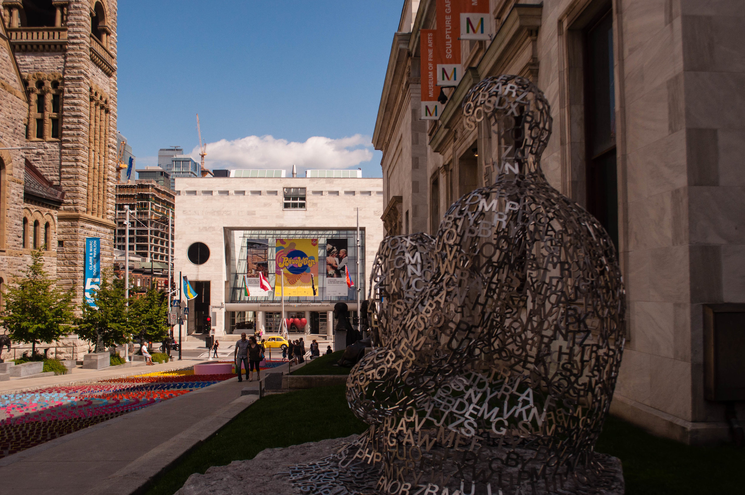 Quartier du musee alley in Montreal with the Fine art museum in the background and a sculpture in the foreground