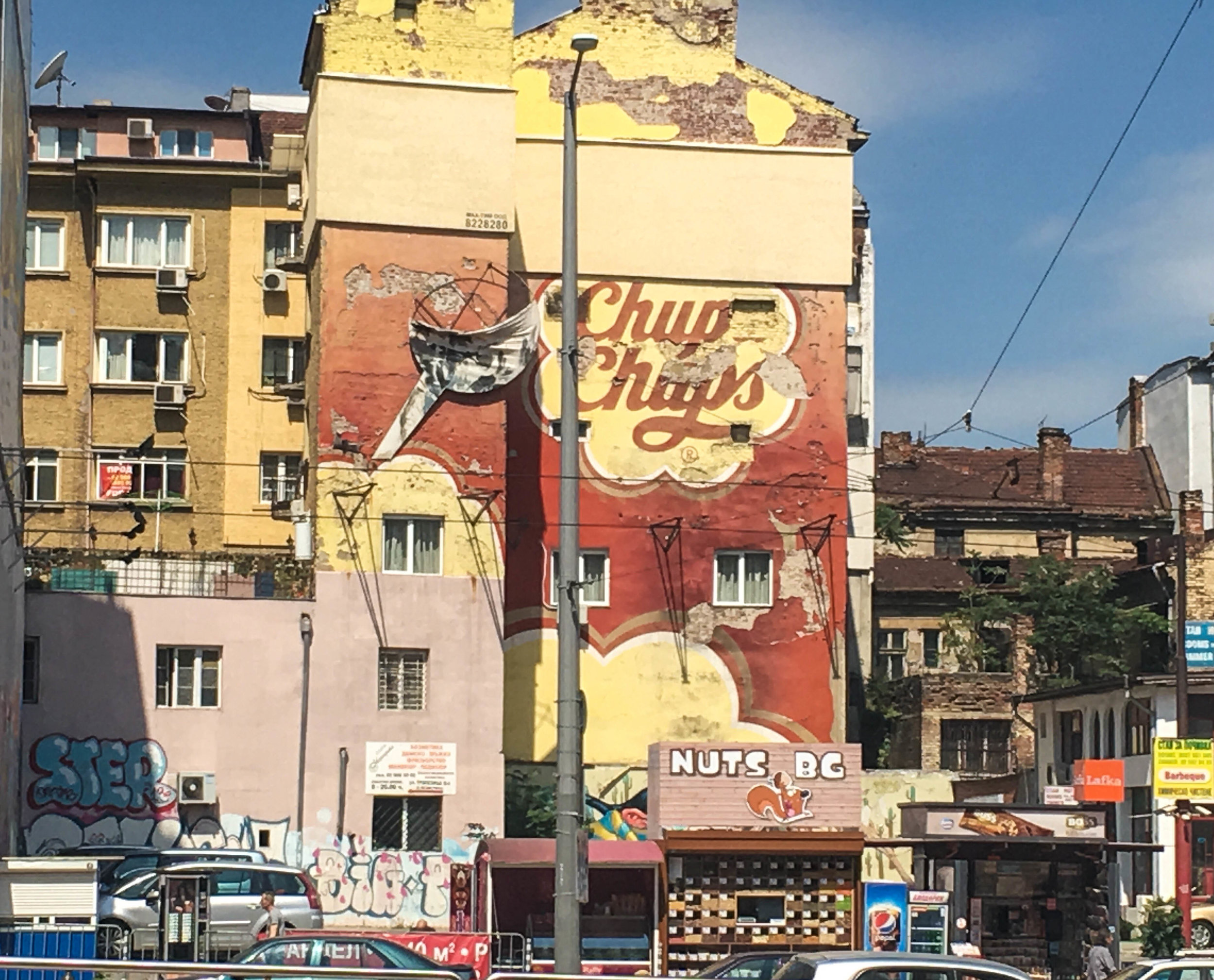 Sofia itinerary, Building in Sofia (Bulgaria) with a Chup Chups decaying mural and a nut stand.