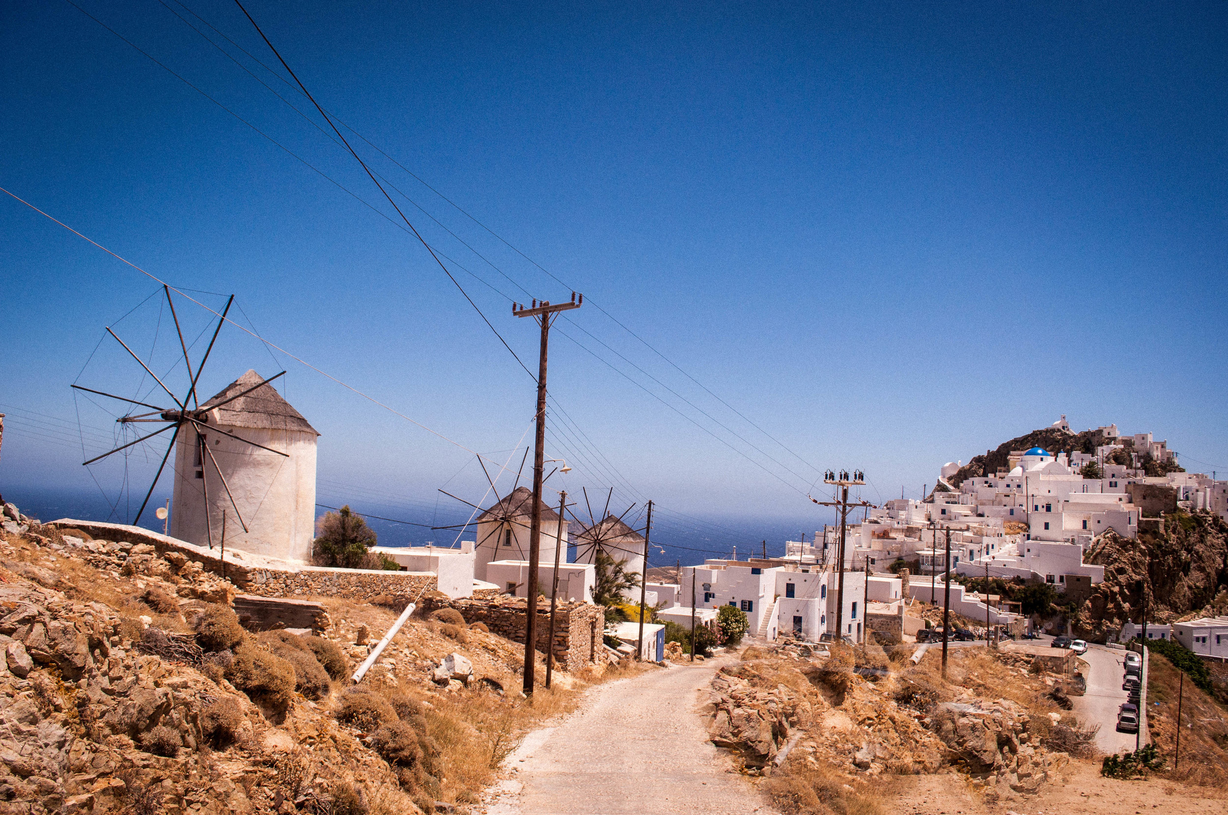 Image of the island of Serifos with its traditional architecture of white buildings and blue dome roofs on the churches and wind mills