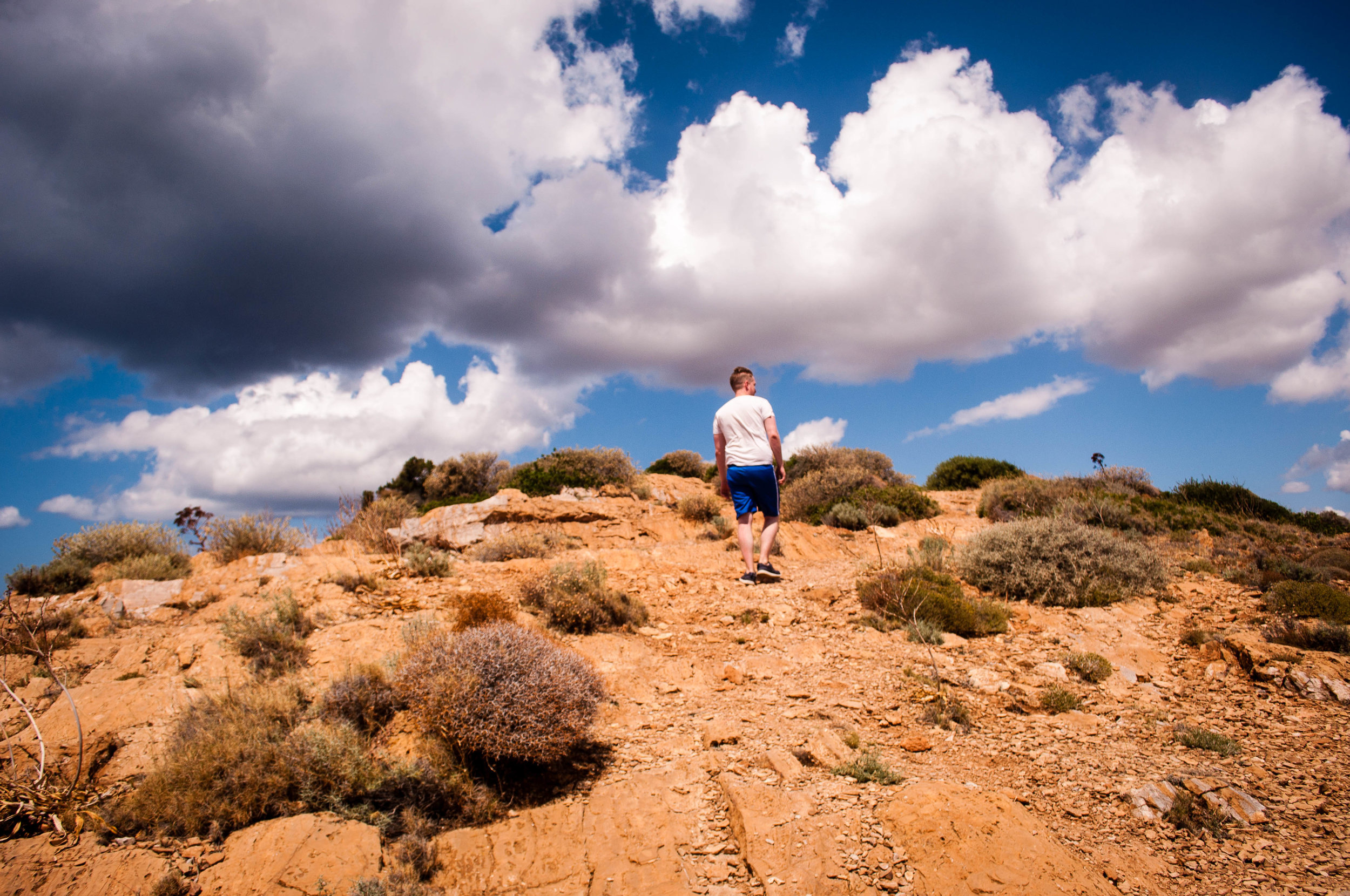 Blue sky with clouds with a white man walking near a cliff on a terracotta ground  in Sounion (Greece)