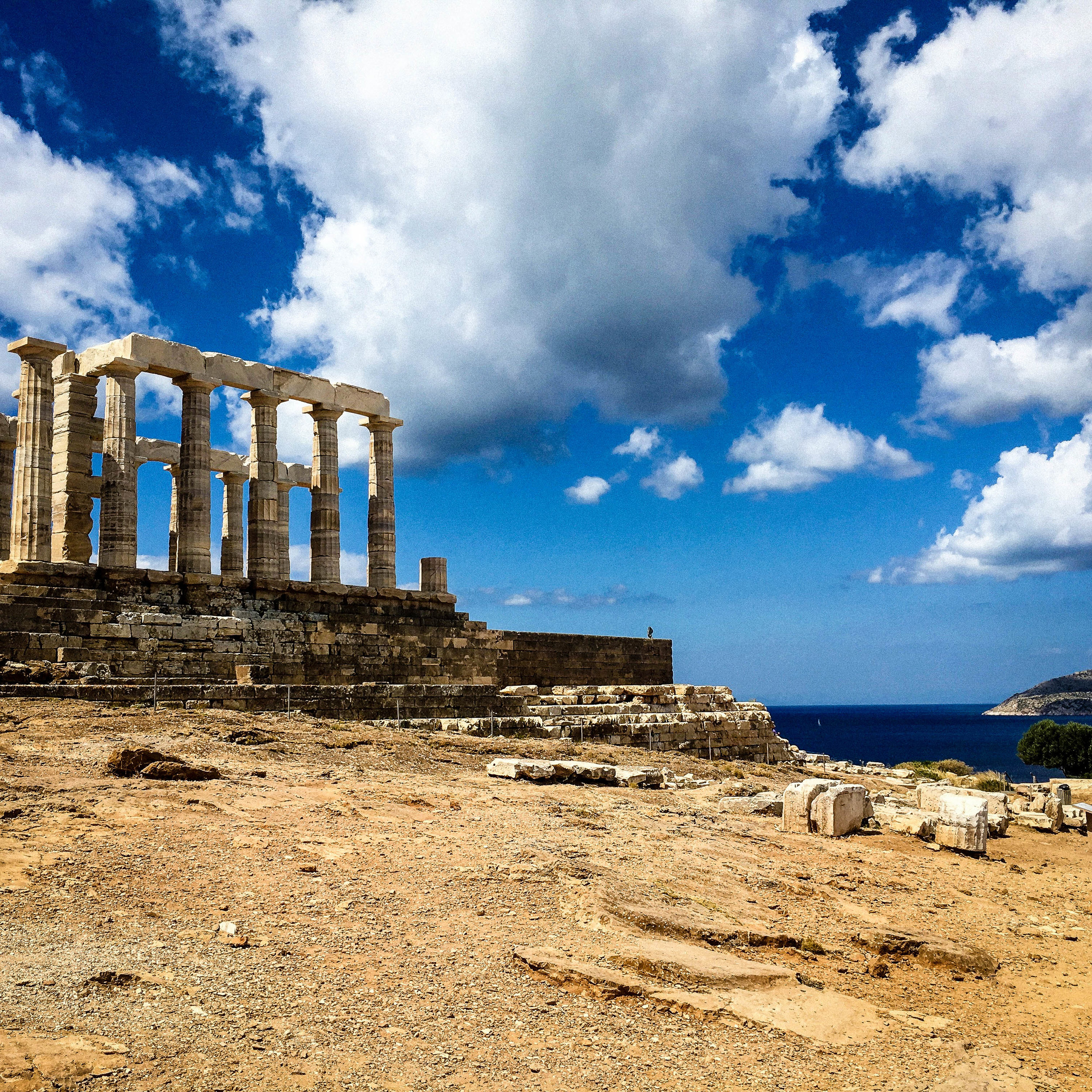 """Blue sky with clouds, and the remaining ruins of the temple of Sounion. This image is a good representation for the article """"how to avoid tourists in Greece"""""""