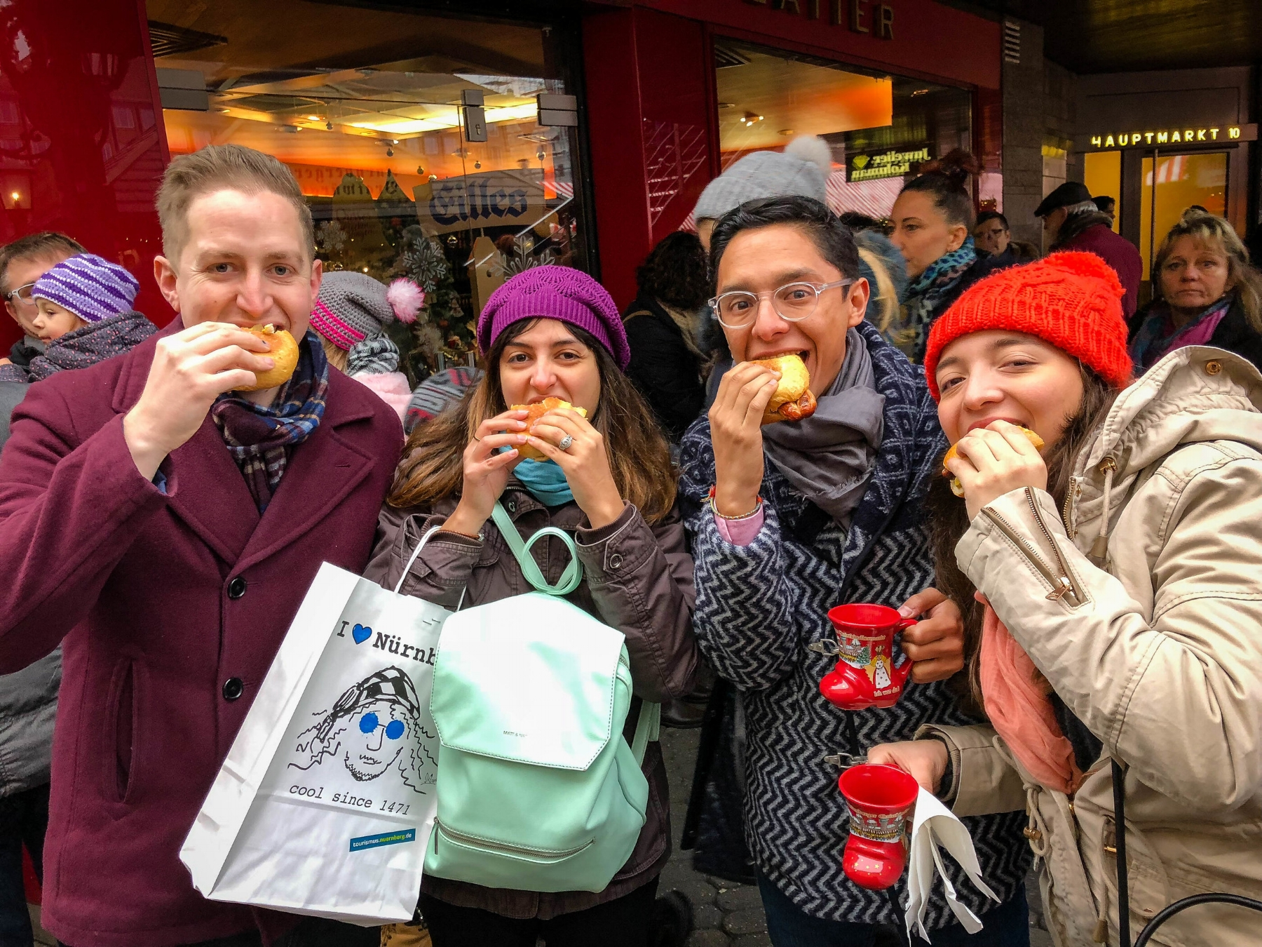 Images of a group of latinos in theNuremberg Christmas market eating Nuremberg grilled Sausages