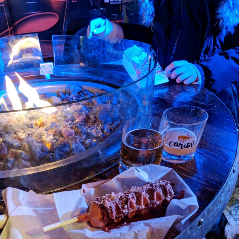 Fire pit in the festival with Cocktail glasses with the Caribu festival logo and waffles. The Festival is a spirit festival close to Montreal in winter