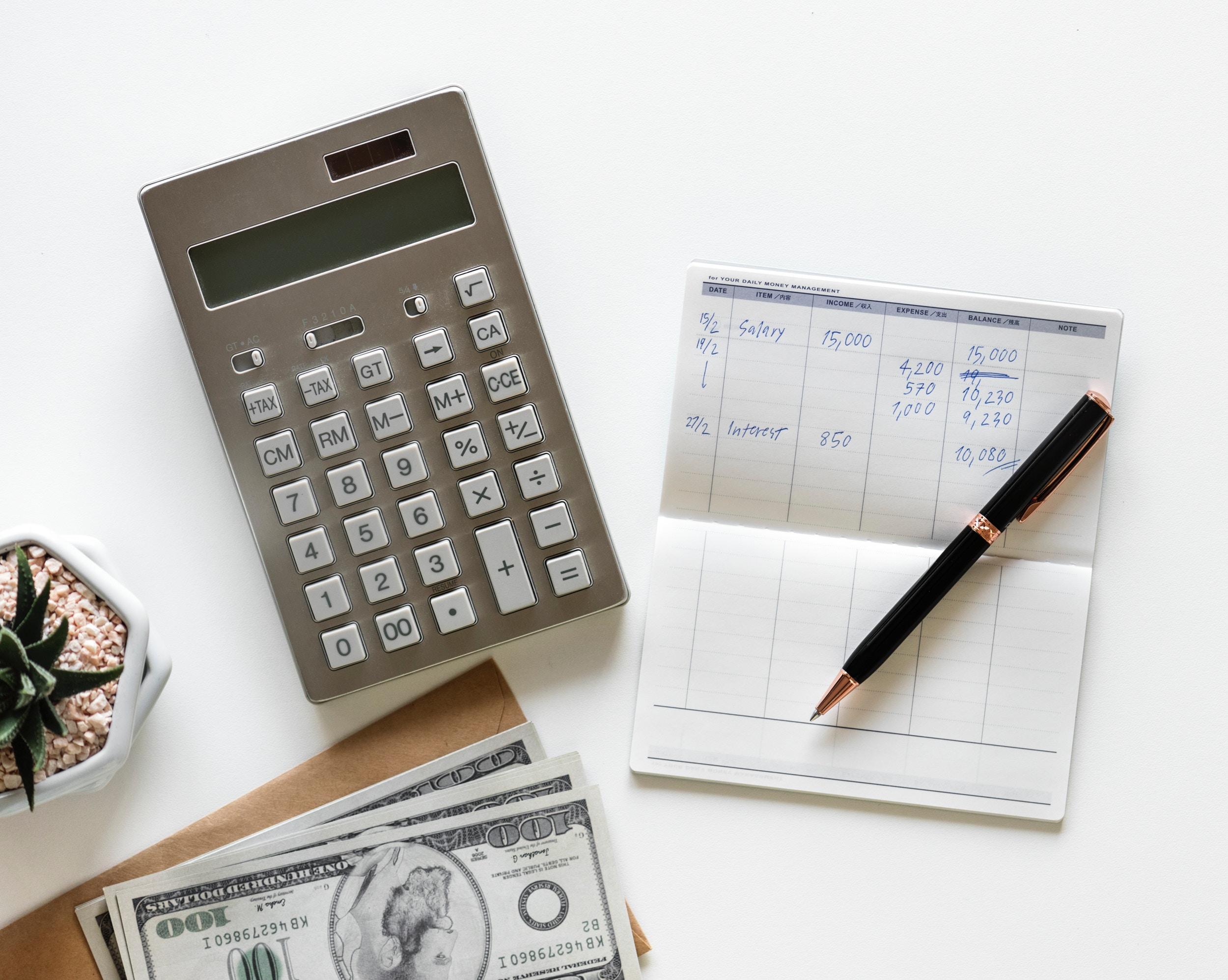 Vacation savings plan. Flat lay of money, calculator