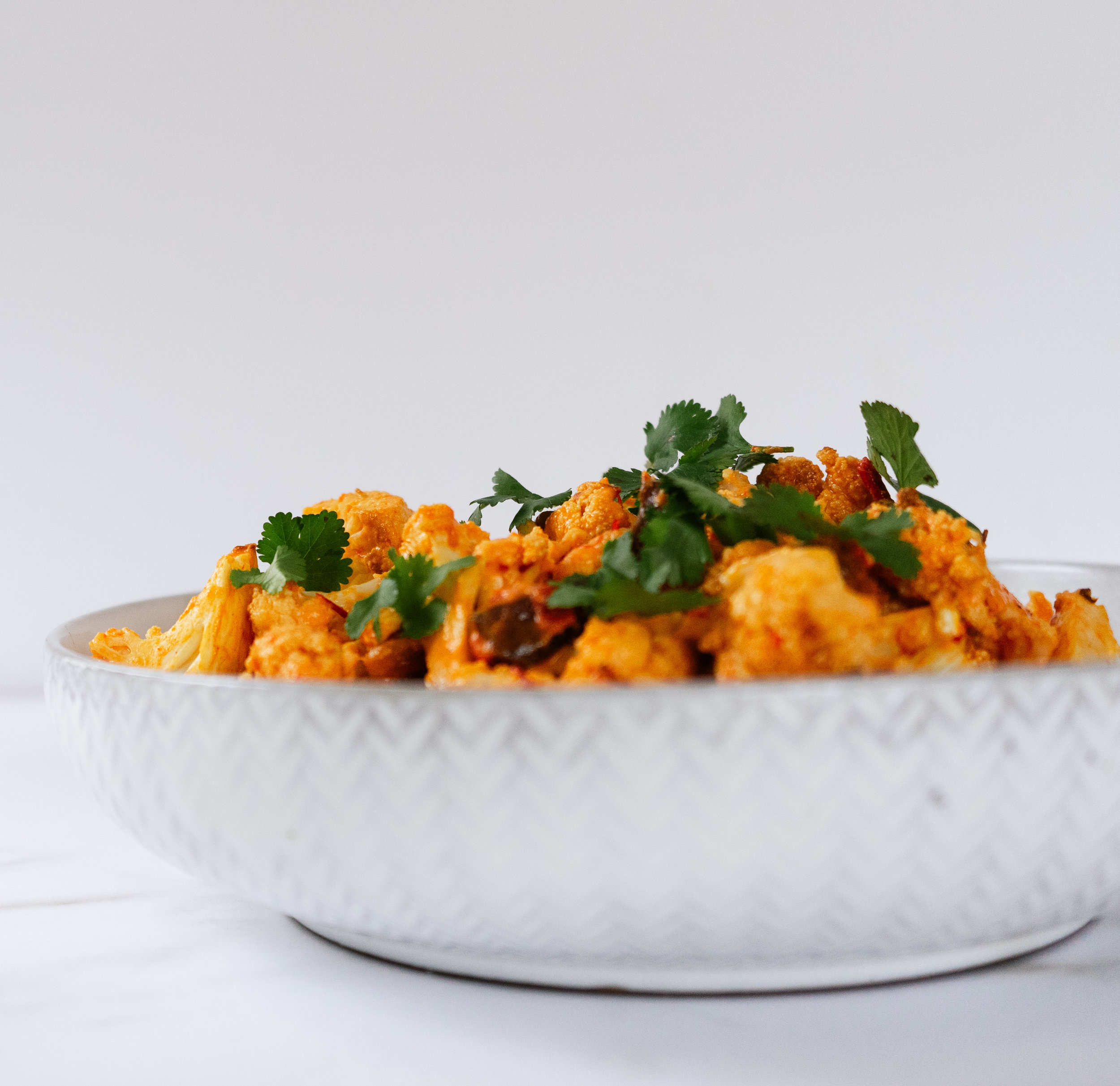 Tahini and harissa roasted cauliflower is a delicious and satisfying whole30 and paleo friendly side dish. It is the perfect addition to any cut of meat or veggie bowl.