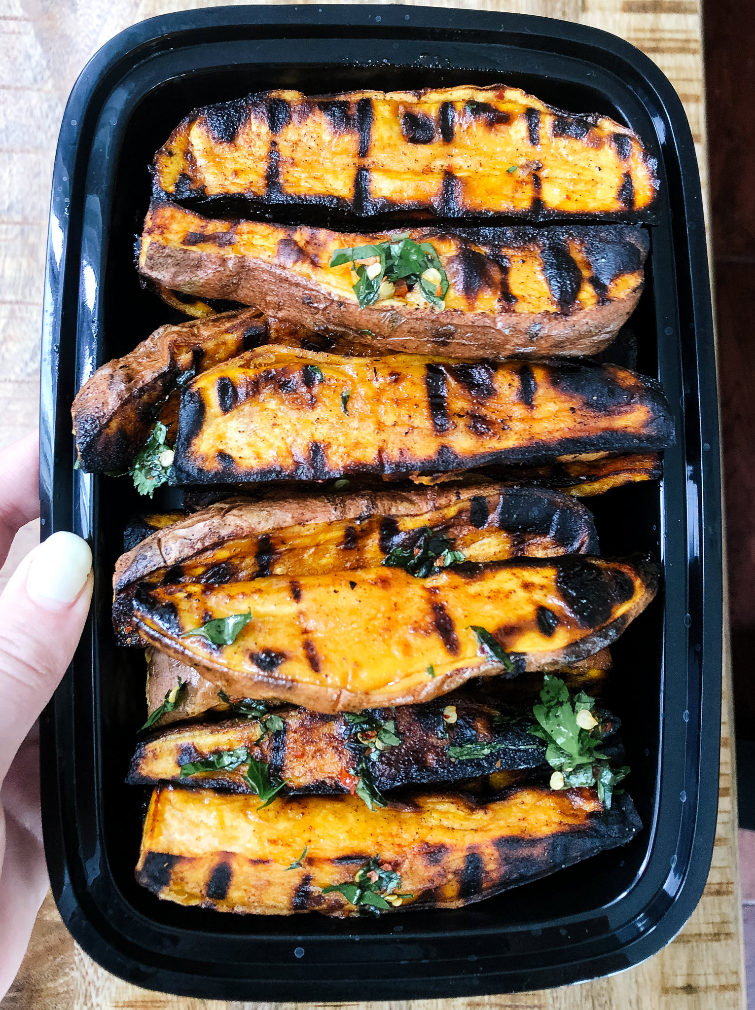 Grilled sweet potato wedges with mixed her dressing is  a simple summer side dish that will round out any barbecue. This healthy, whole30 and paleo friendly side dish comes together in less than 30 minutes and is delicious with burgers, hot dogs, steaks or grilled fish!