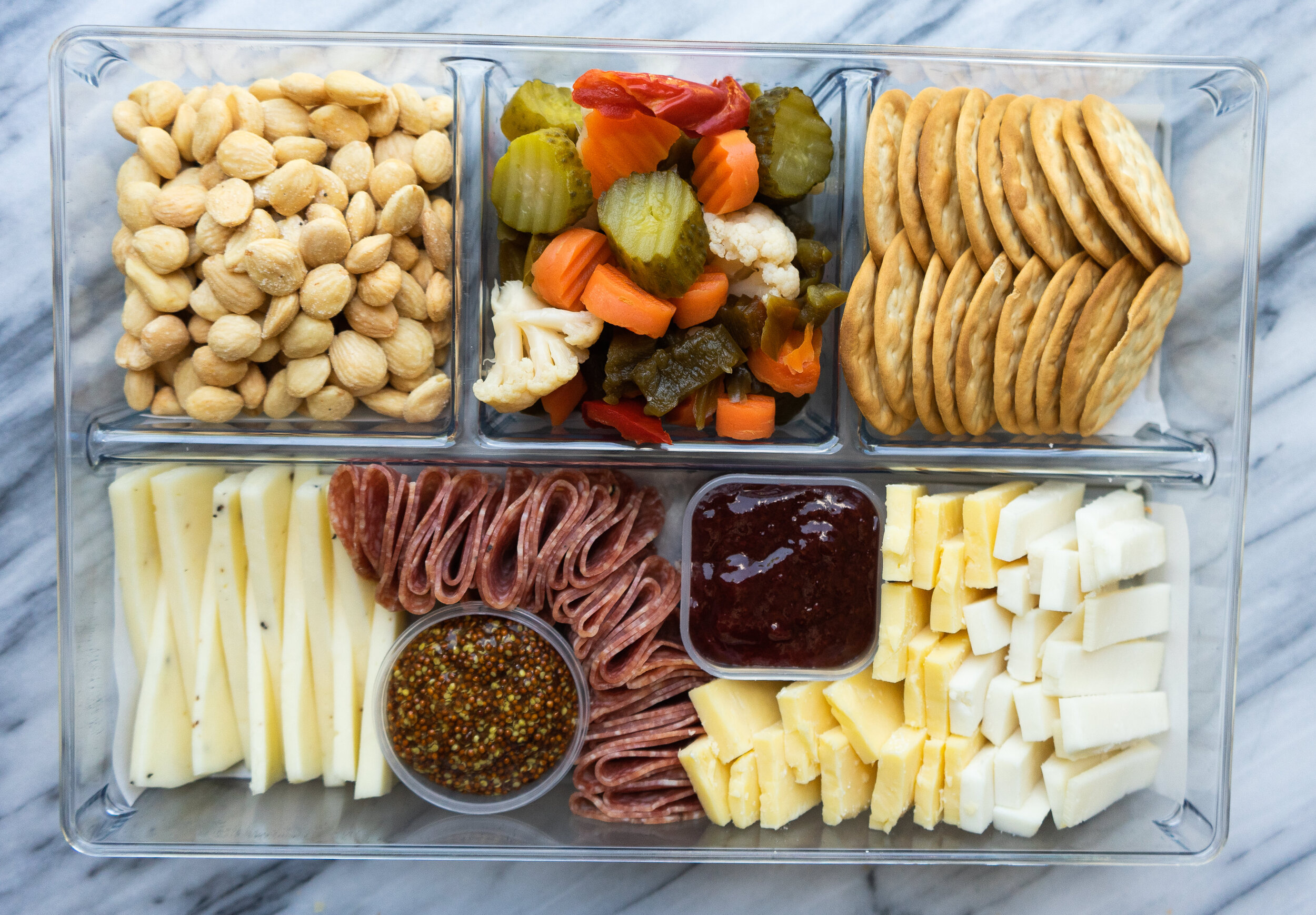 Take your cheese boards on the go with this simple trick for making a Trader Joe's cheese board on-the-go. I love to make charcuterie boards and cheese plates of all kinds and you can use a simple drawer organizer to take them as a party appetizer or football tailgating snack!